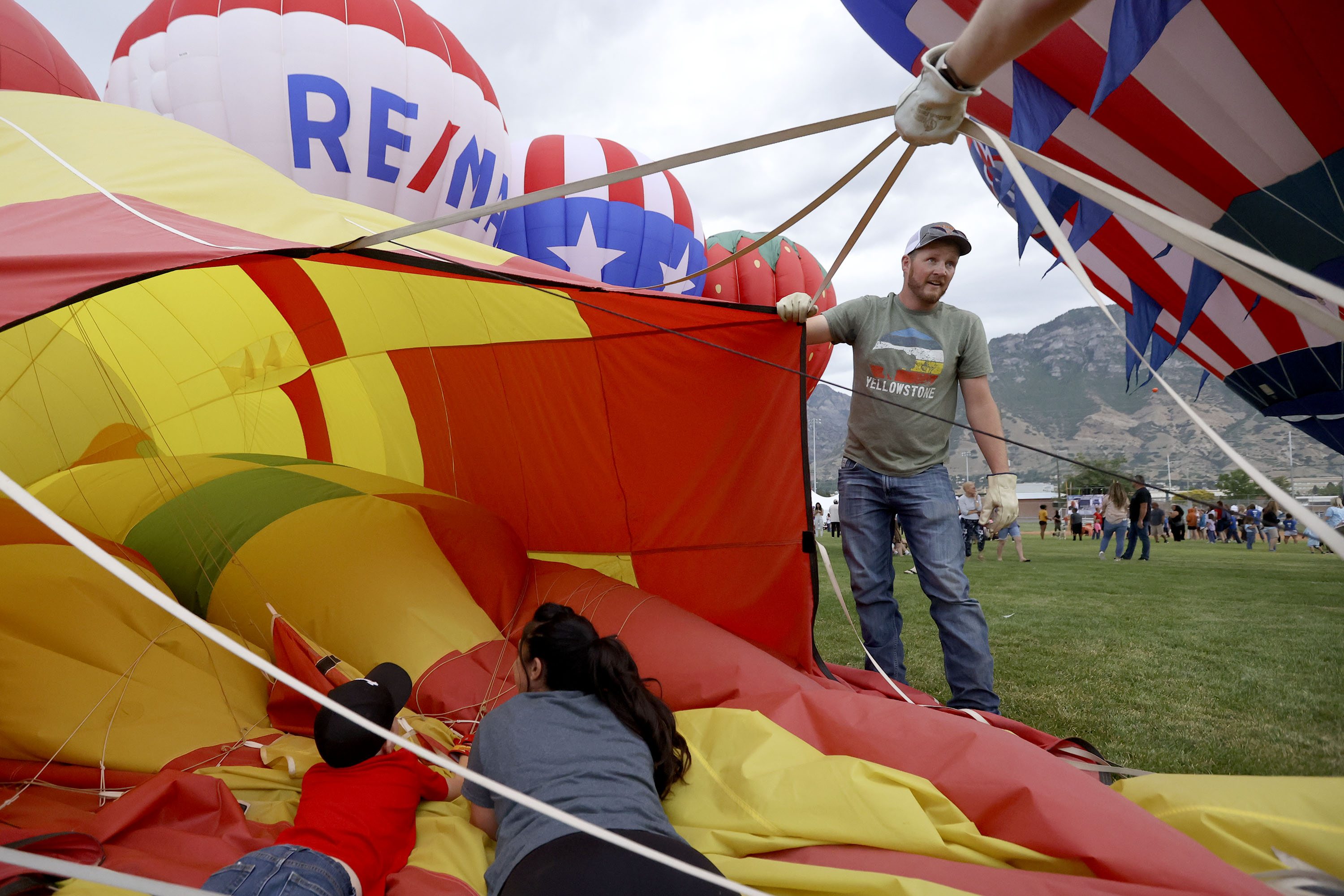 Mike Evans helps take down the Chili balloon as Cooper Johnson and Johnna Monforte weigh it down during Balloon Fest on Bulldog Field in Provo on Friday, July 2, 2021. The balloons could not fly due to weatherbut were inflated for display.