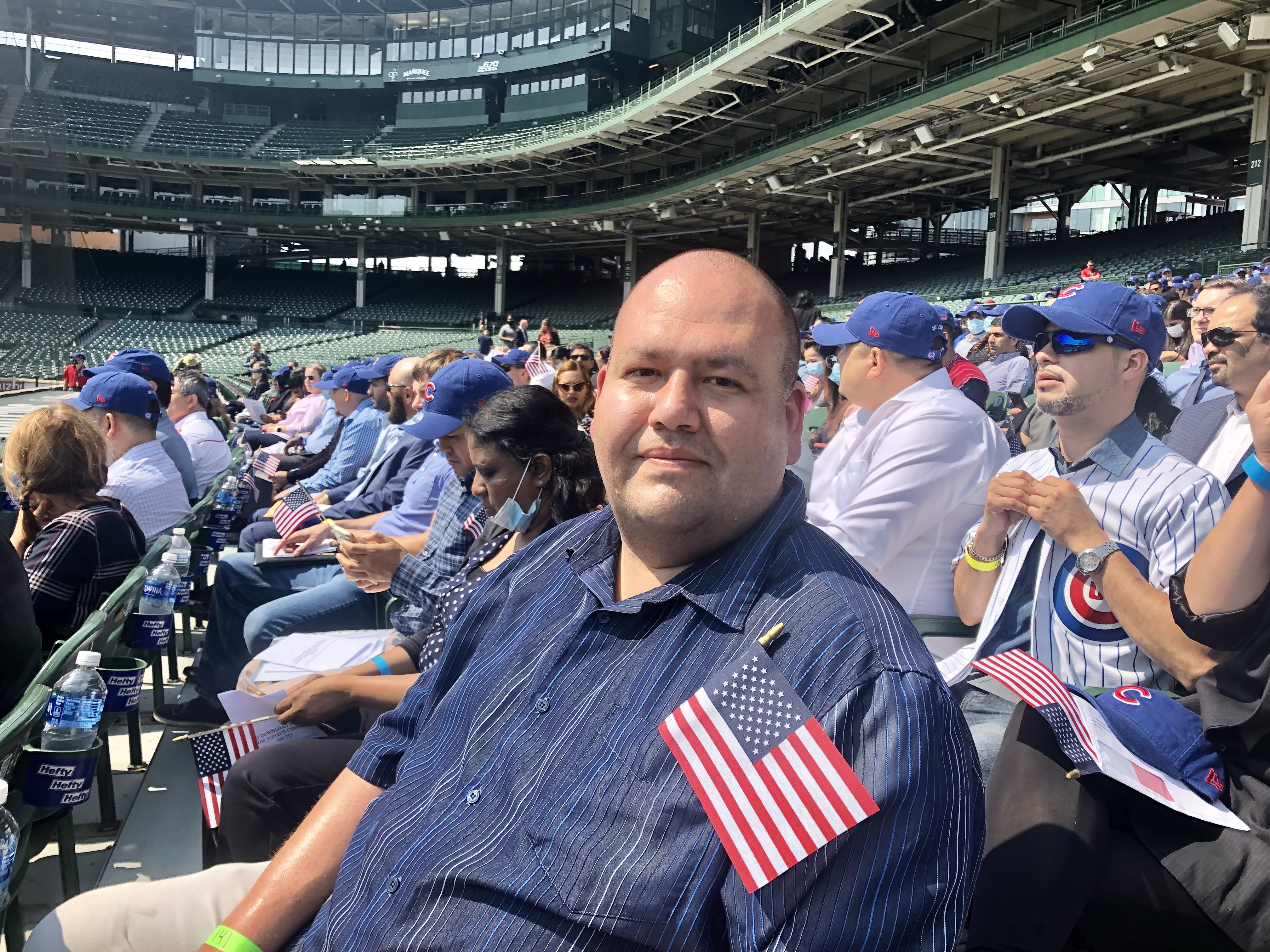Hector Perez sits in the stands near the third base line at Wrigley Field Friday. He was one of 172 people who became new citizens at a special naturalization ceremony. Perez, 38, is eager to see visit relatives in Mexico and not worry about being let back in the United States.