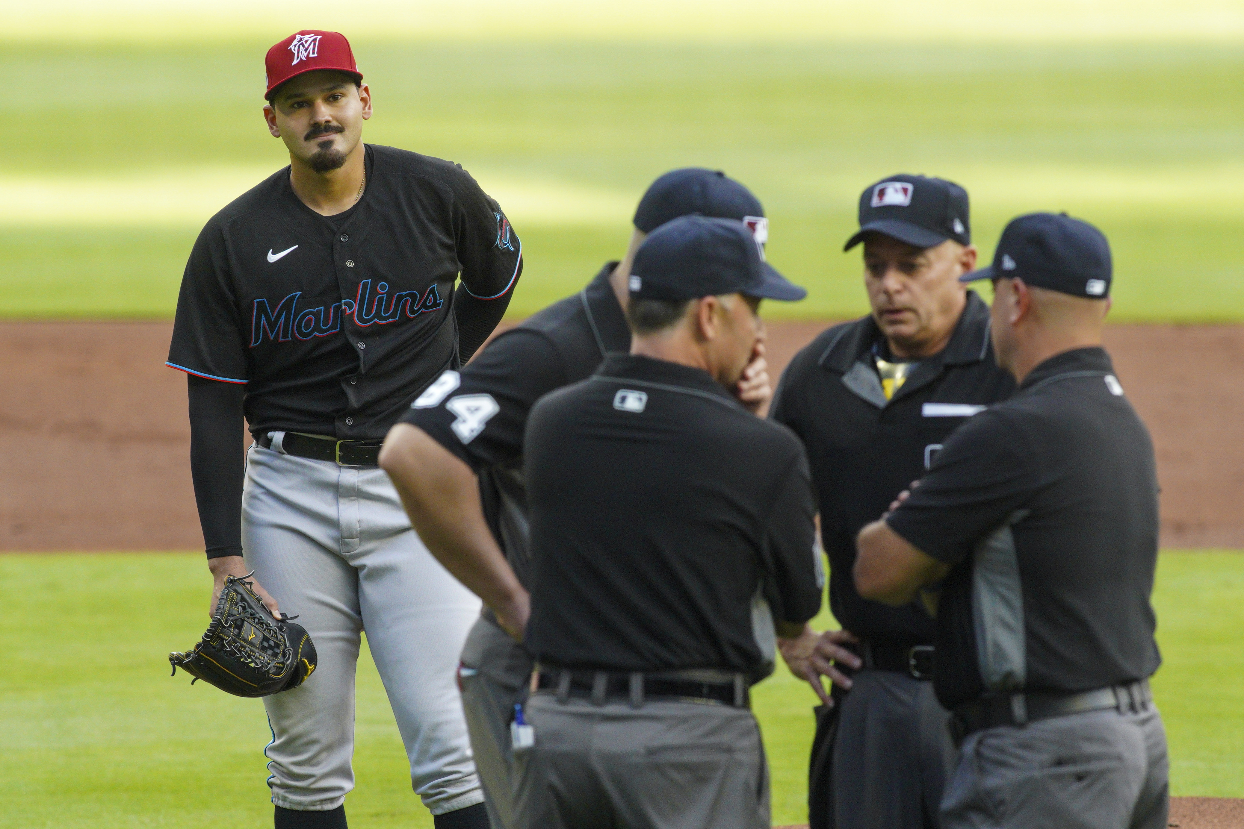 Miami Marlins starting pitcher Pablo Lopez (49) looks on as umpires talk after Lopez hit Atlanta Braves right fielder Ronald Acuna Jr.