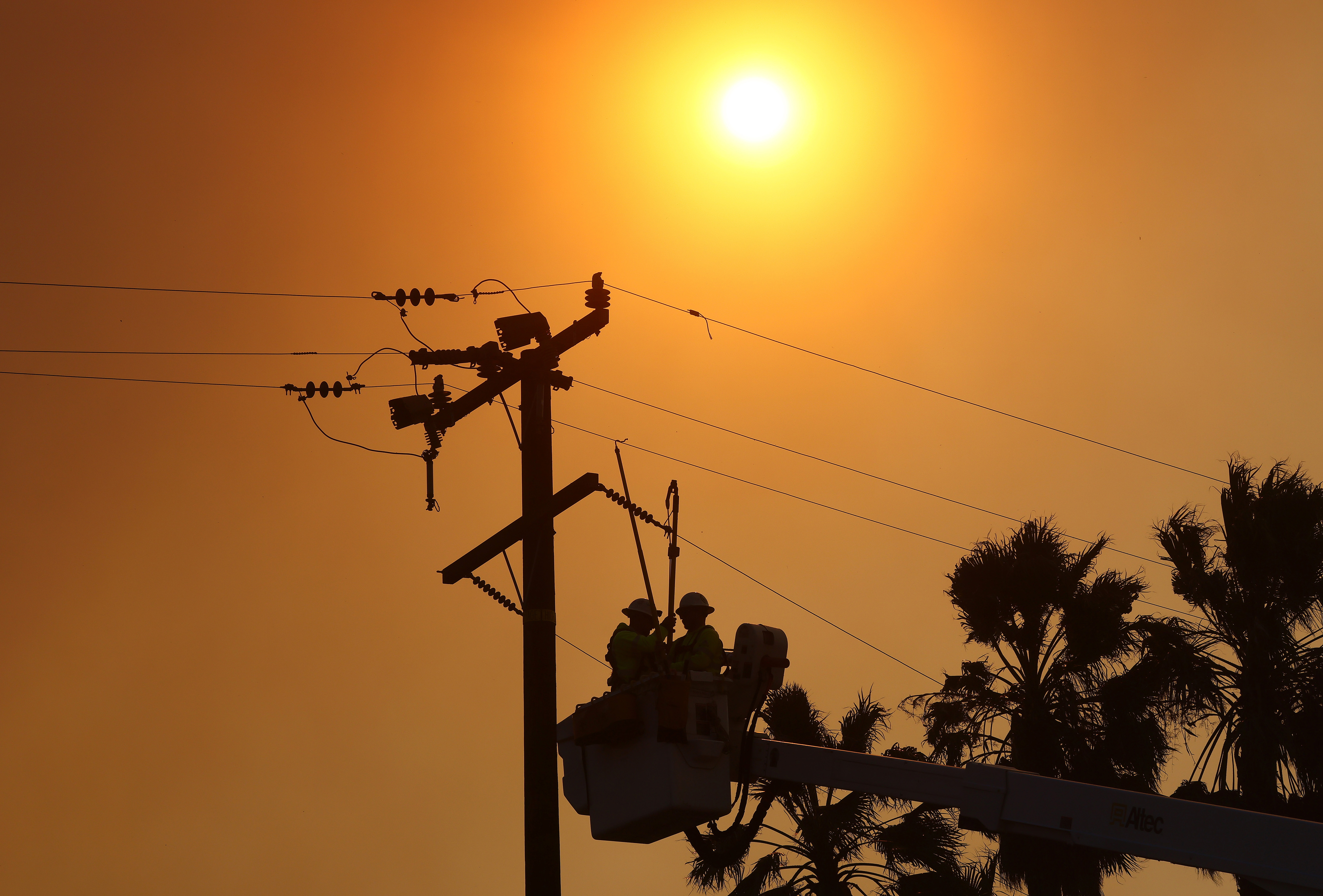 Workers in a cherry-picker basket approach a power pole while a bright sun glares overhead.