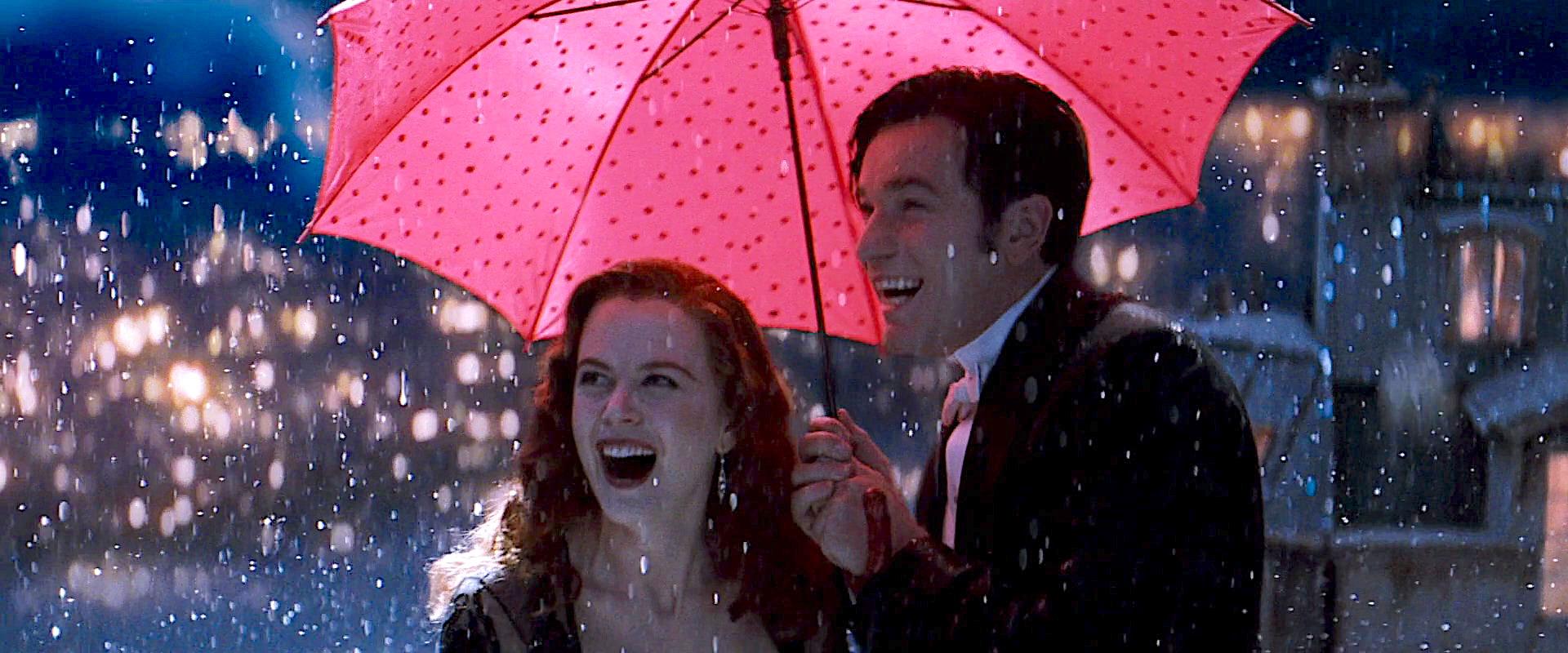 Nicole Kidman and Ewan McGregor under a pink umbrella together in Moulin Rouge