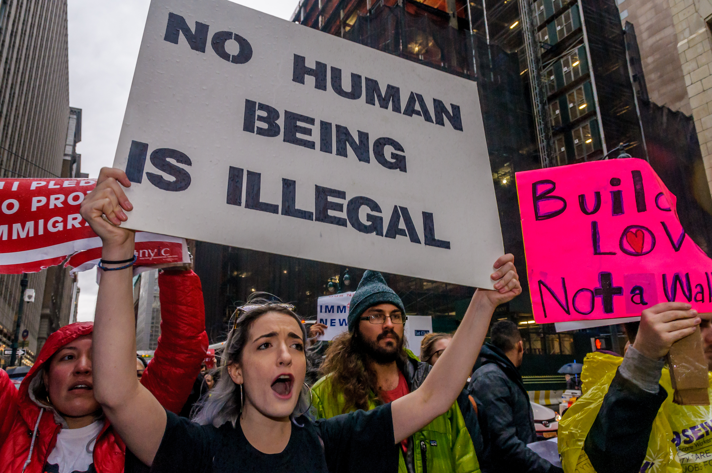 """A protester in a crowd on a city street holds up a sign that reads, """"No human being is illegal."""""""