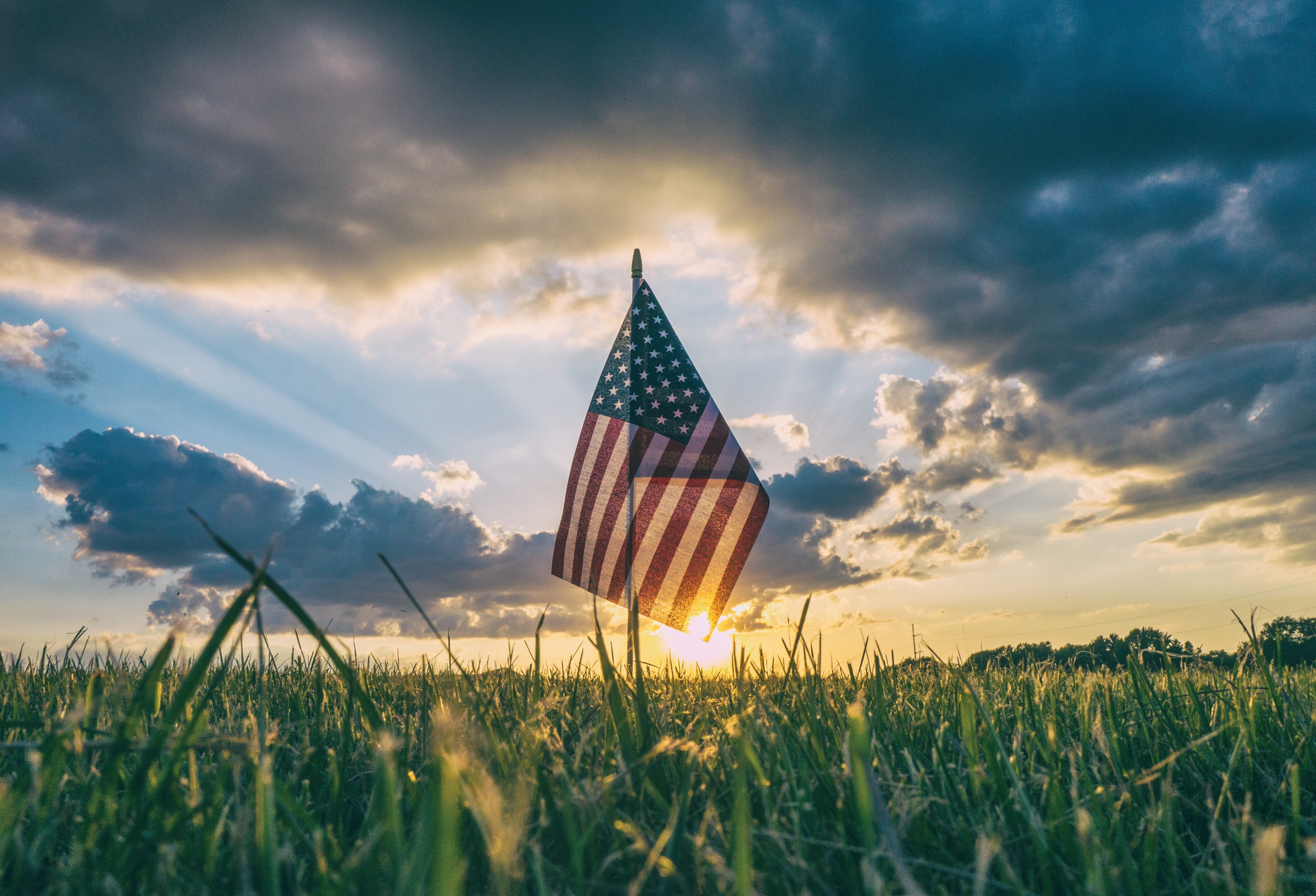 An American flag in a field at sunset.
