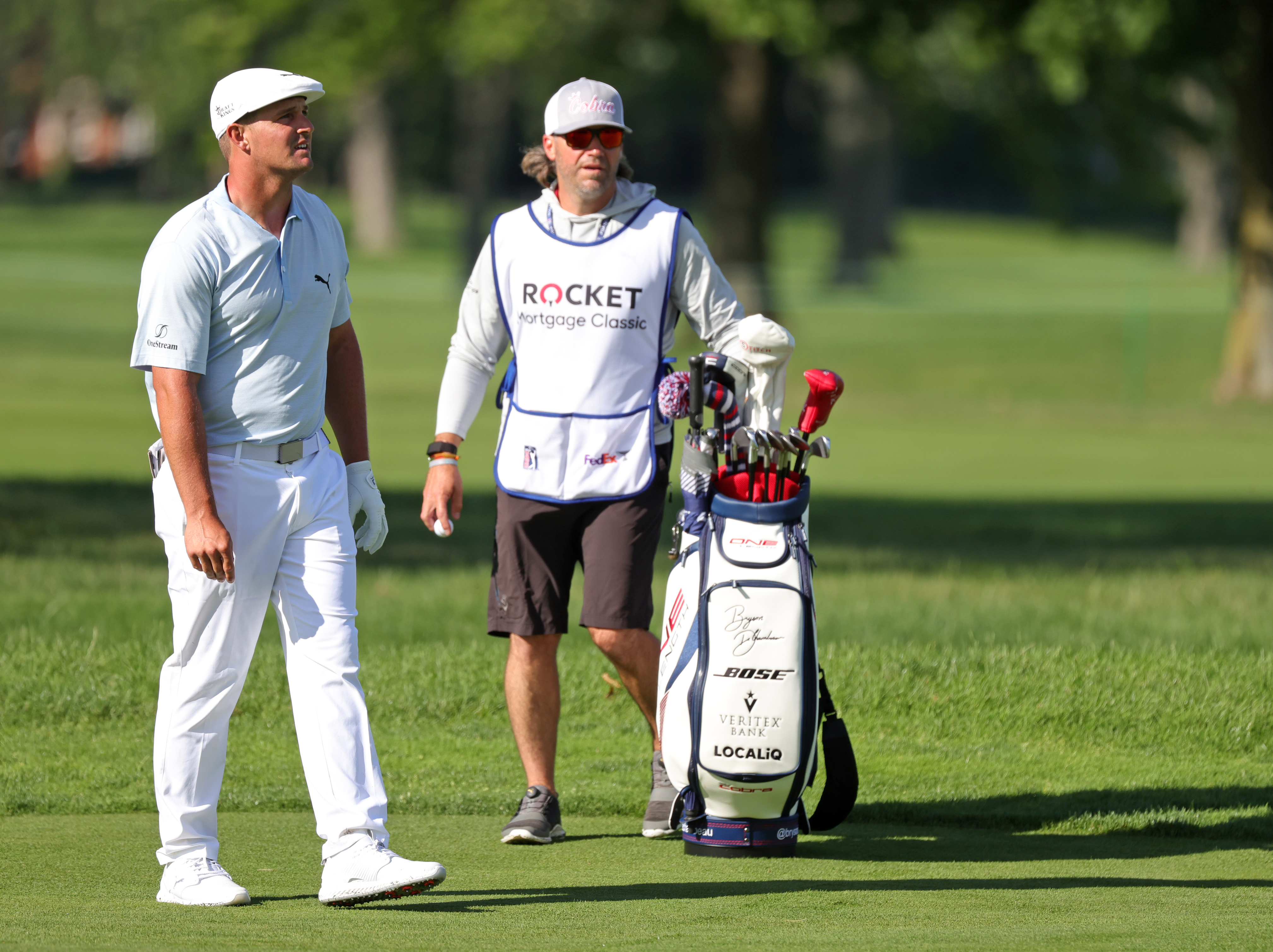 Bryson DeChambeau and caddie Ben Schomin prepare to play a shot during the second round of the Rocket Mortgage Classic on July 02, 2021 at the Detroit Golf Club in Detroit, Michigan.
