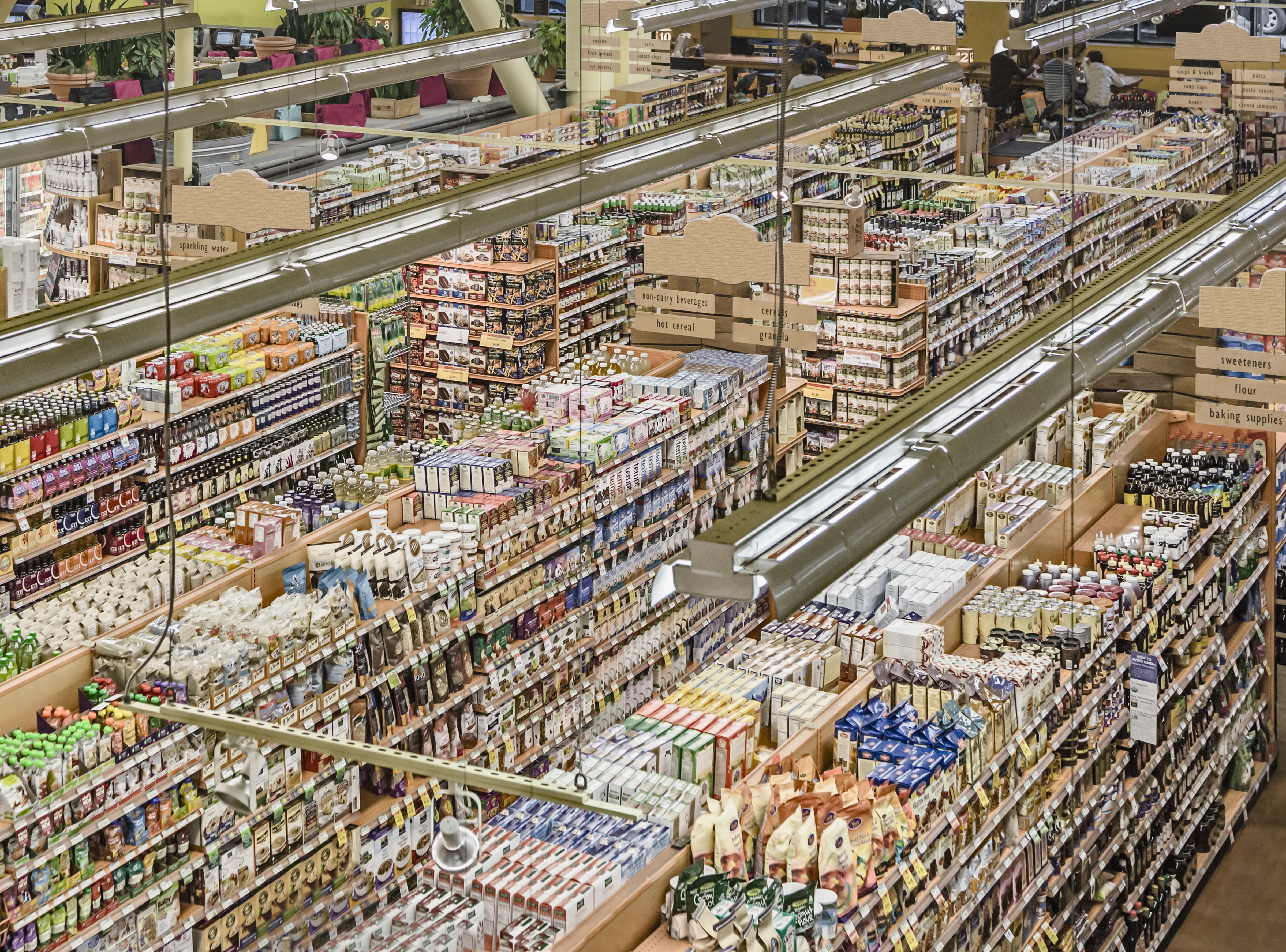 Aisles in a well-stocked grocery store, shot from above.