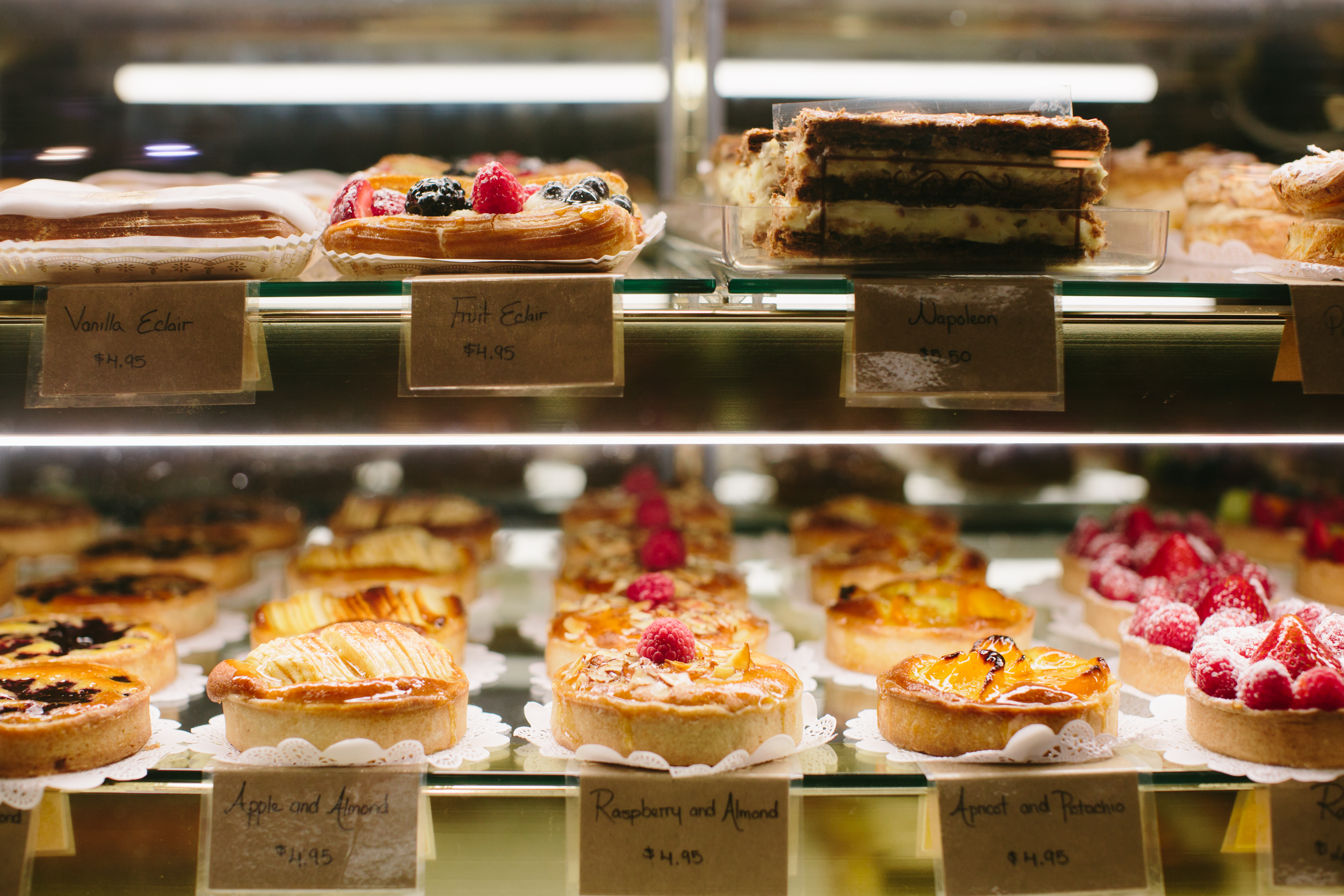 Two shelves of five rows colorful custard fruit tarts, eclairs, and Napoleons at Saint-Germain Bakery in Atlanta displayed in a lighted glass case. Tags placed in front of each row display the names of items along with the prices