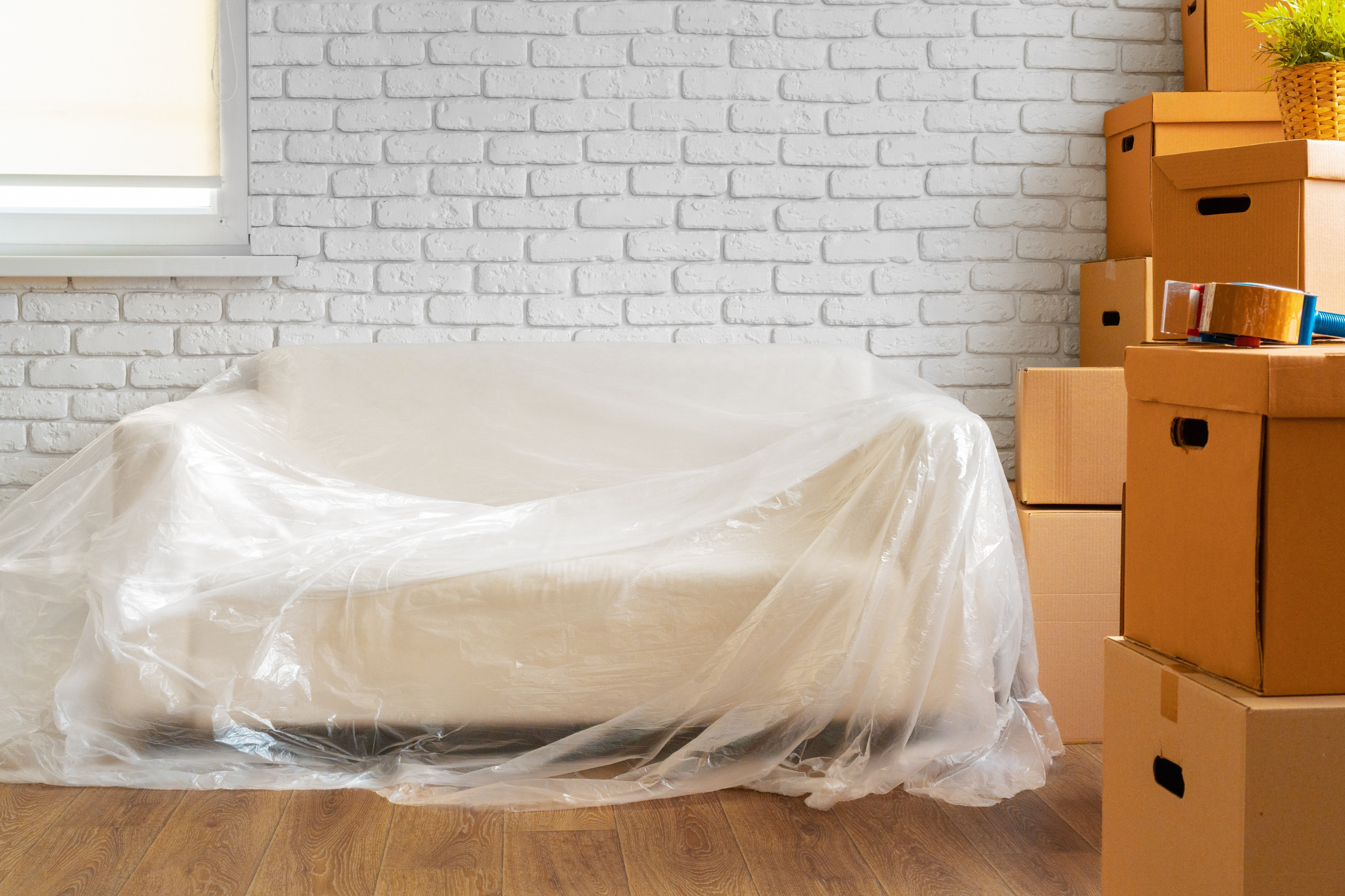 A white couch inside a home with clear wrapping over it, brown cardboard moving boxes, and packing tape.