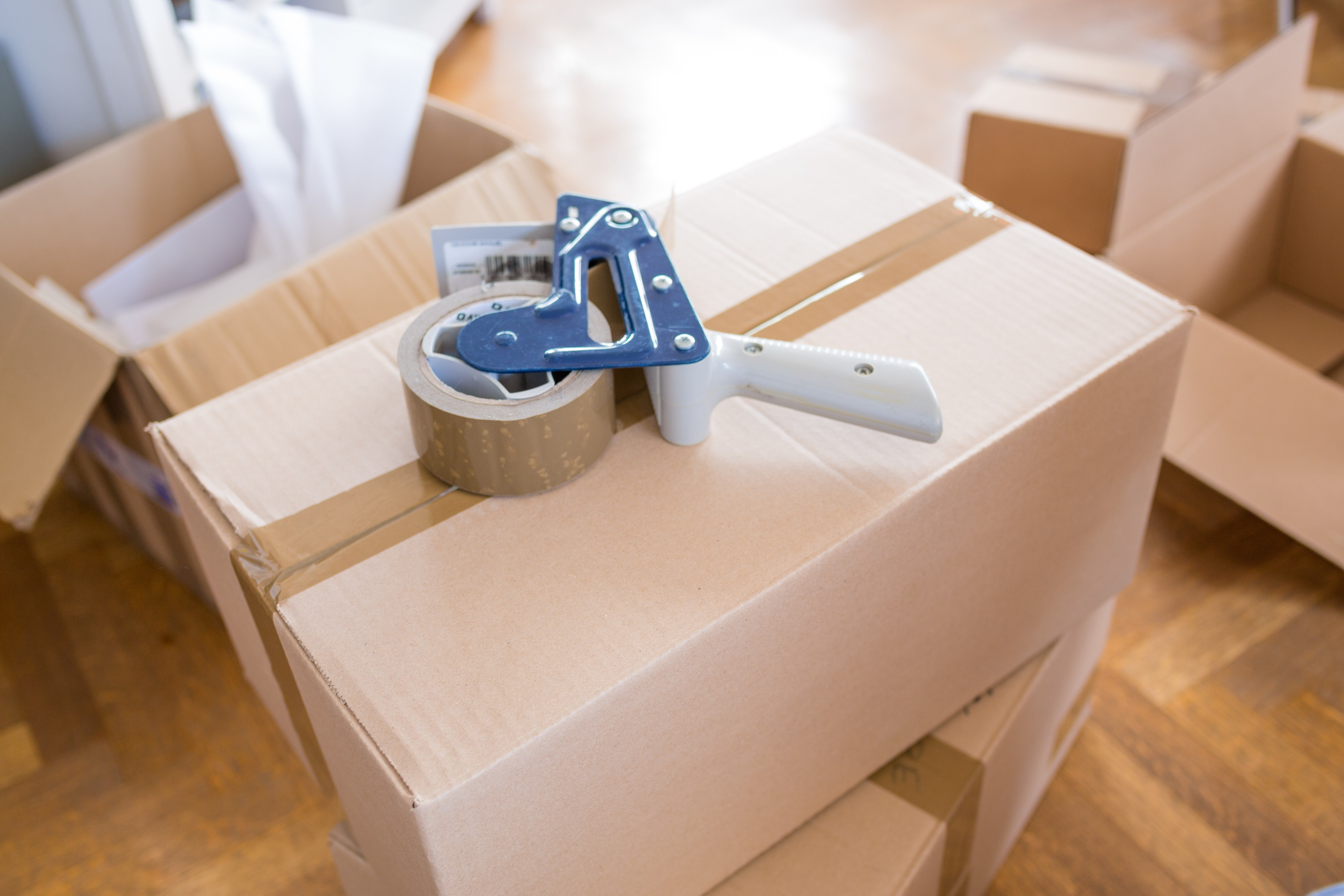 A brown cardboard moving box amongst other moving boxes inside a home with a roll of packing tape on top.