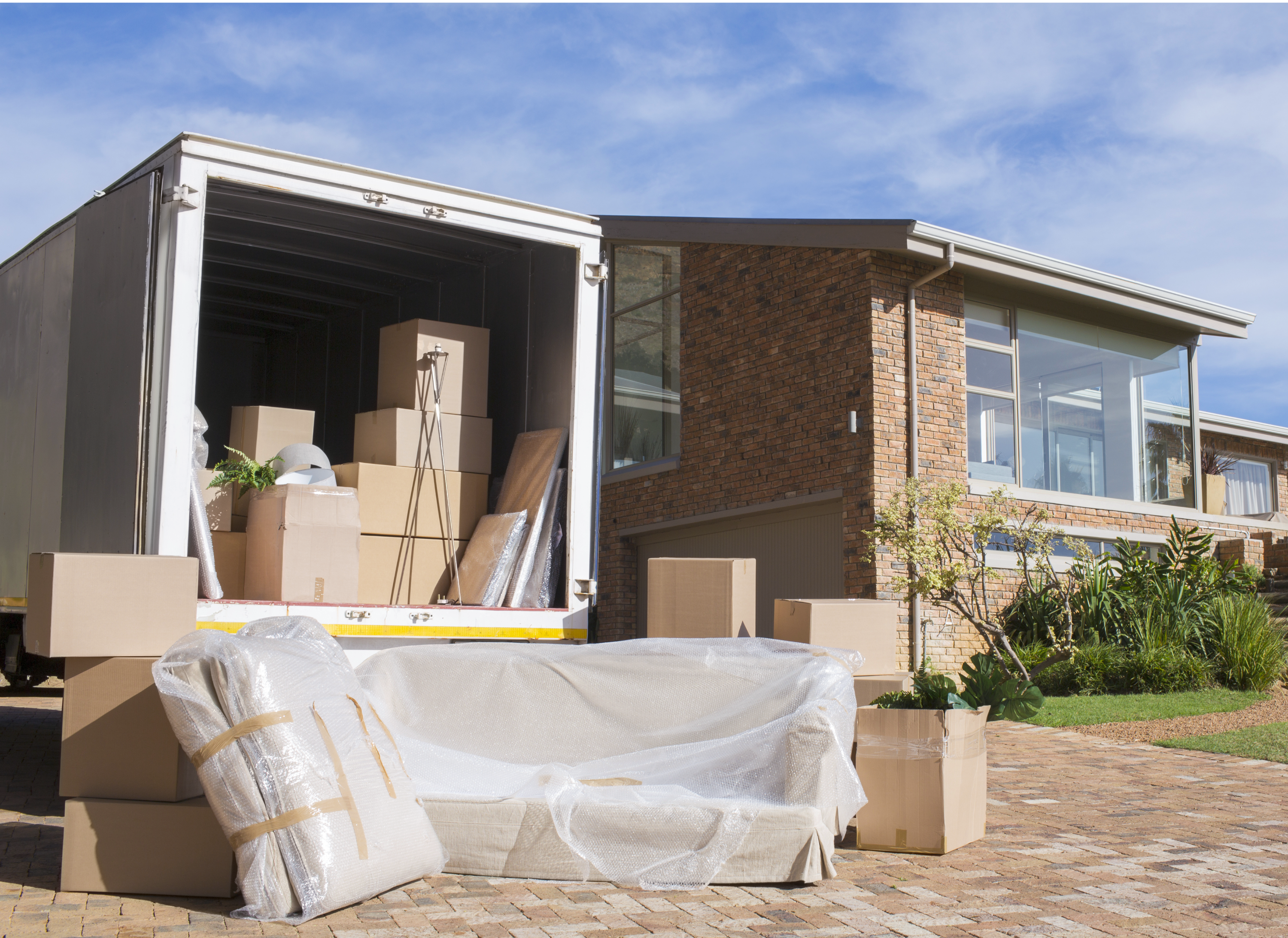 The open back of a moving truck in the driveway of a home with several brown cardboard boxes inside with bubble-wrapped furniture.