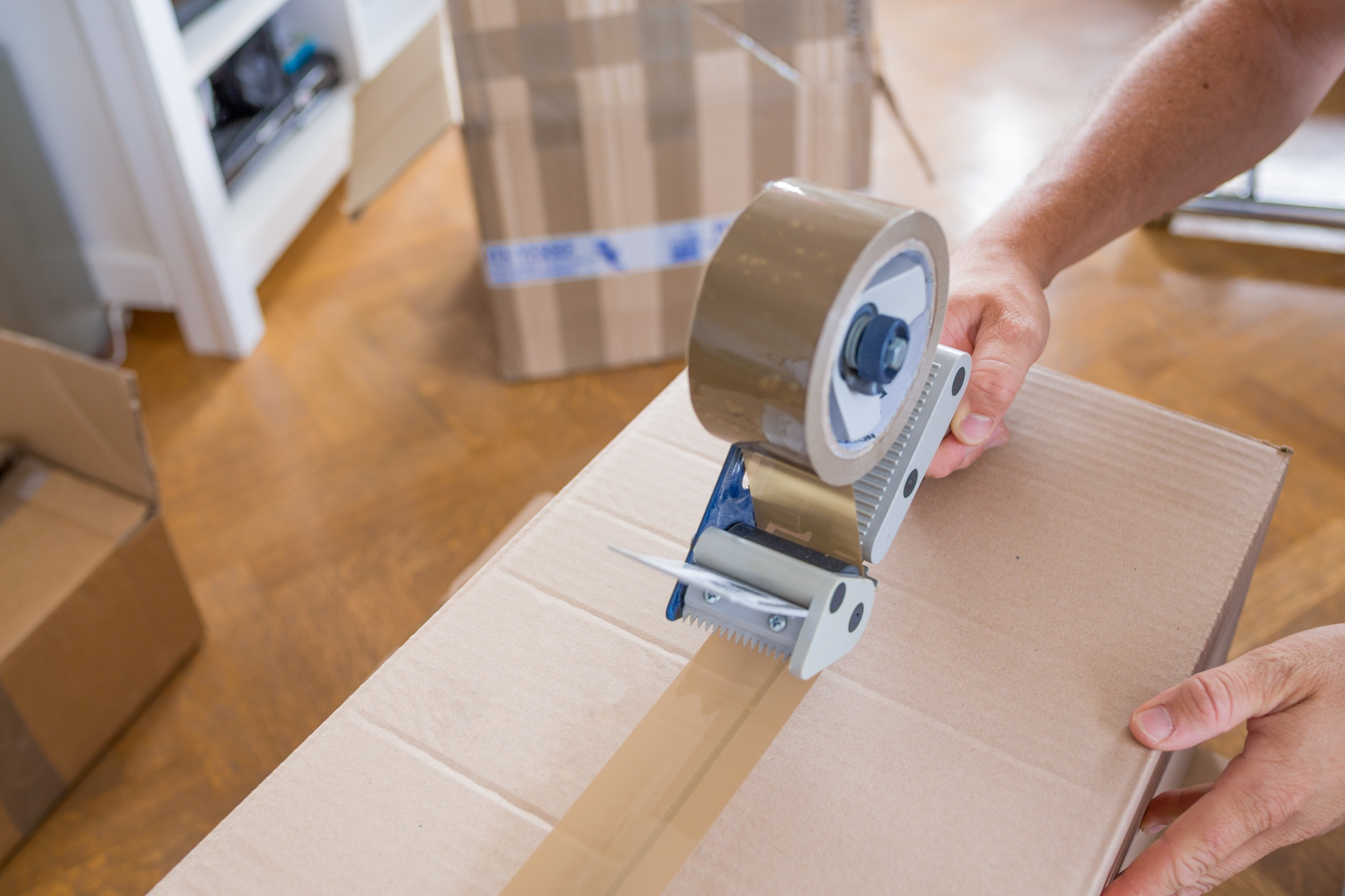A person uses packing tape on a brown cardboard moving house inside a home with hardwood floors.