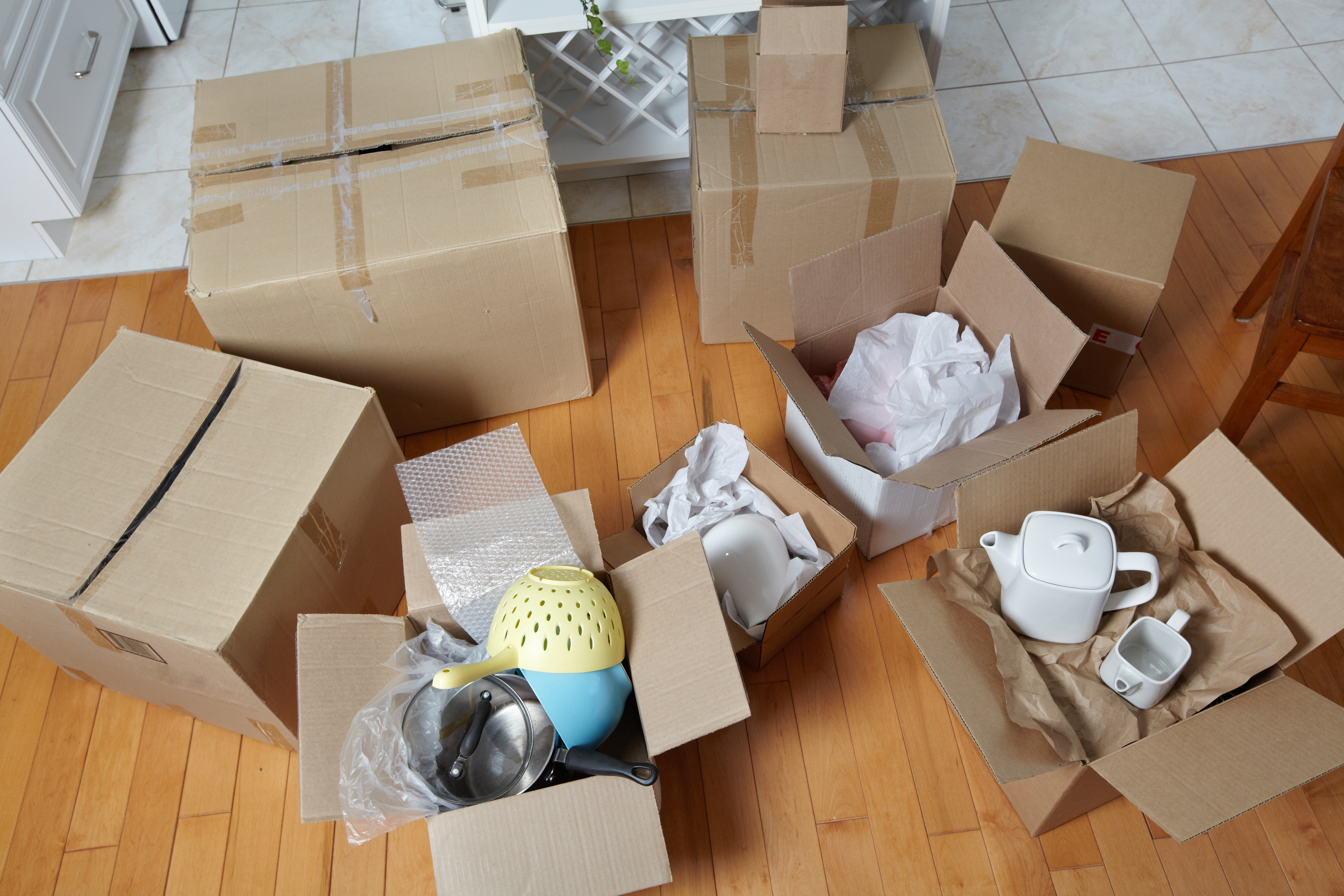 Assorted cardboard moving boxes on the floor with dishes and packing paper.