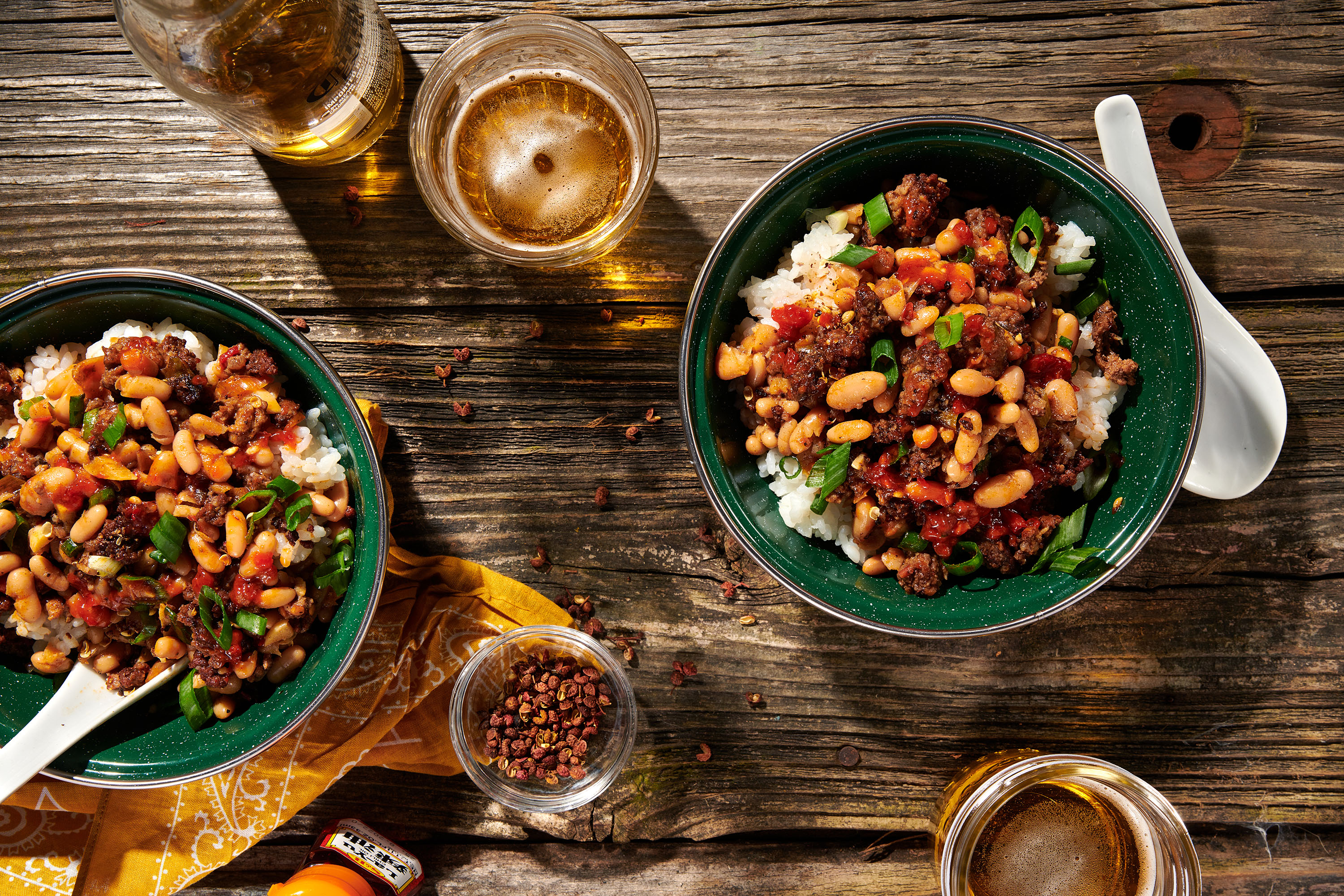 Two bowls filled with mapo beans and white rice, as seen overhead on the top of a picnic table, with spoons and mason jars of beer alongside.