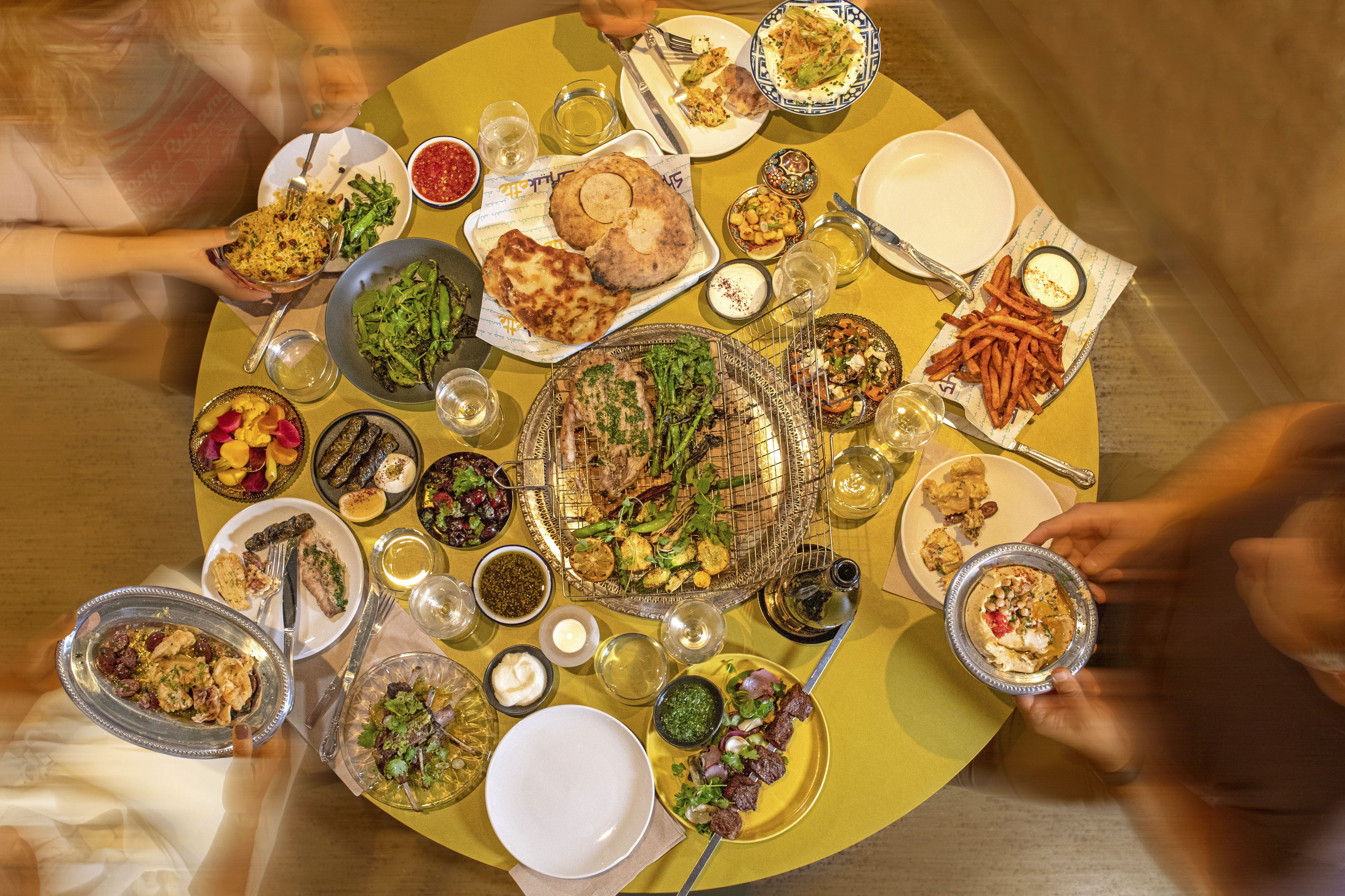 Three people hold plates and dishes around a yellow table filled with spreads of vegetables, meats, breads, and dips