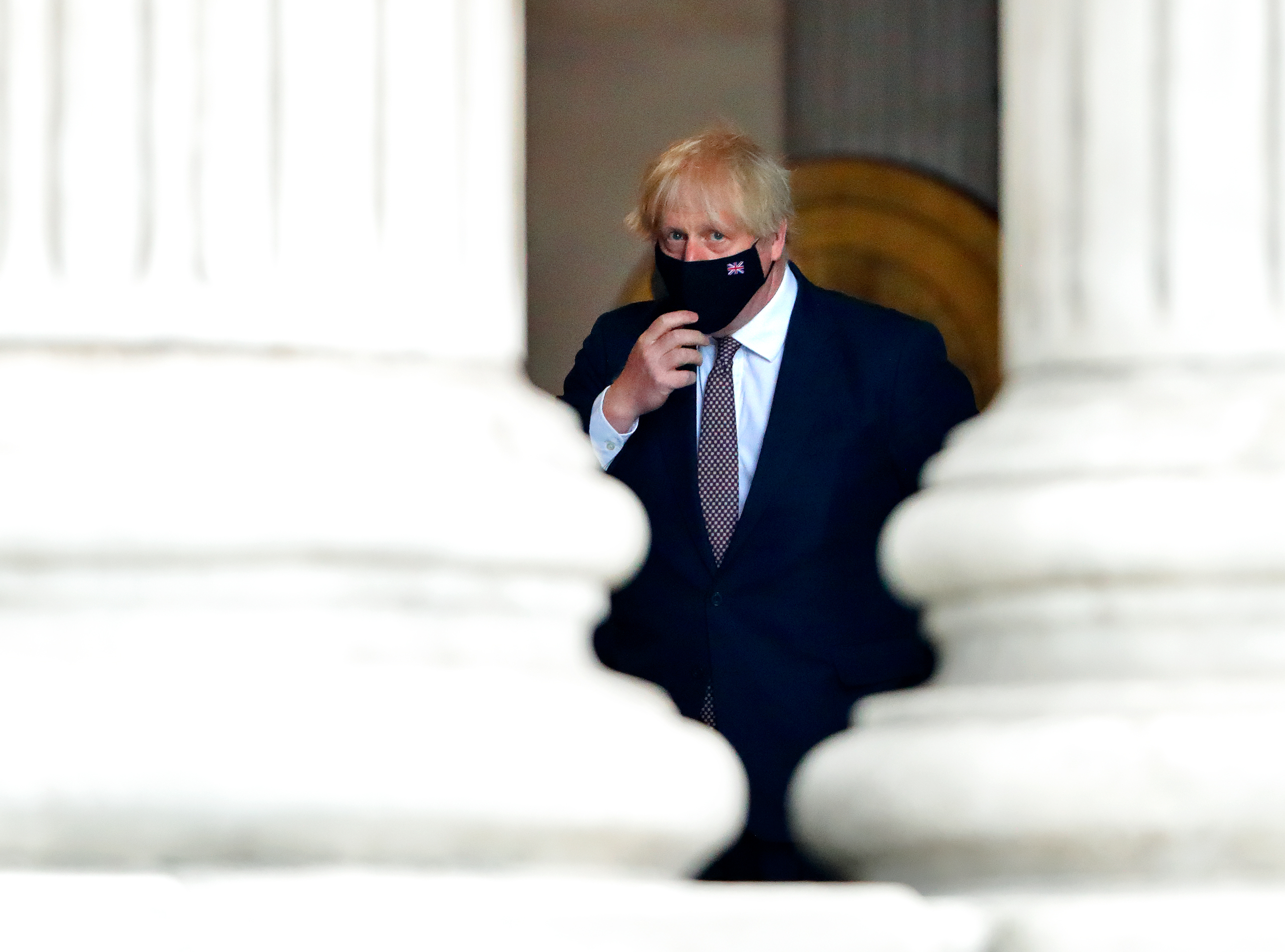The Duke Of Cambridge Marks The NHS' 73rd Birthday with Boris Johsnon looking on behind a mask between two Doric columns