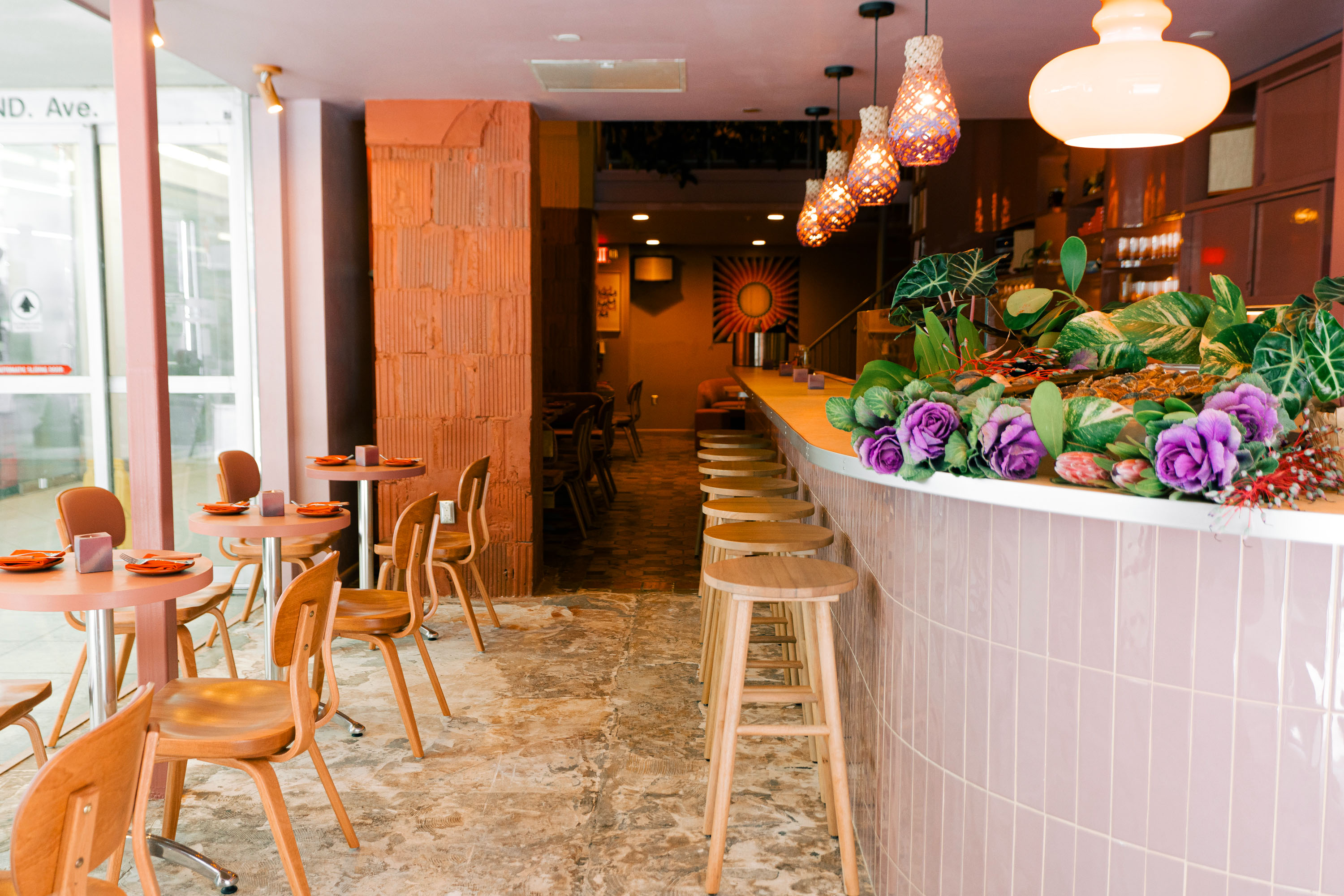 dining room and bar with wooden tables, pink bar area with flowers, vintage lights hanging from the ceiling