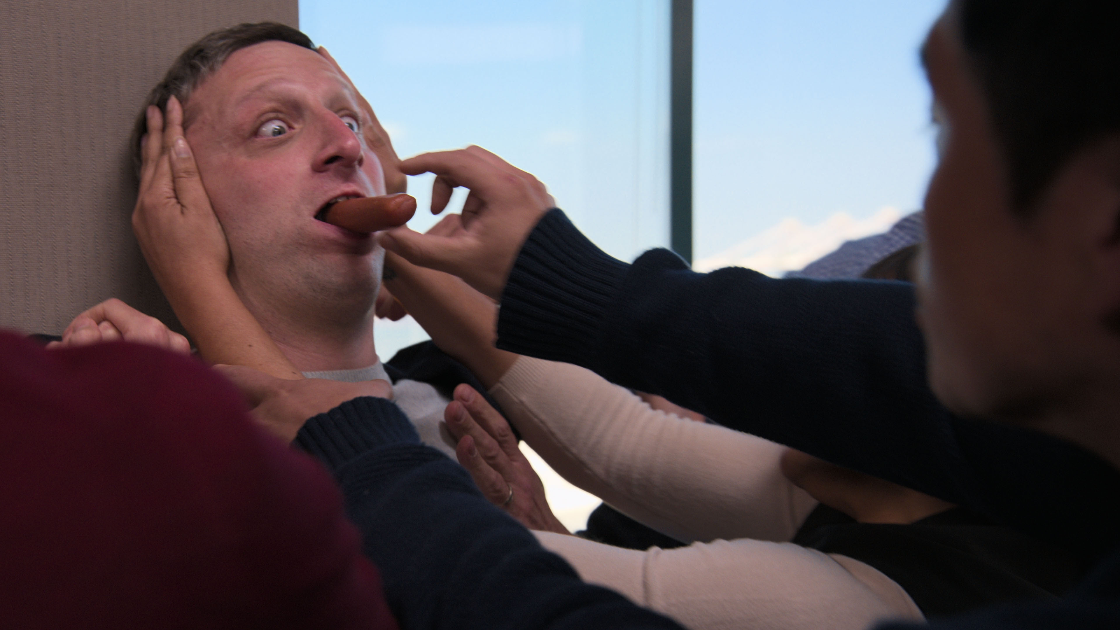 Tim Robinson, backed against a wall with a hot dog sticking out of his mouth, has several co-workers trying to grab the hot dog in a skit from I Think You Should Leave season 2.