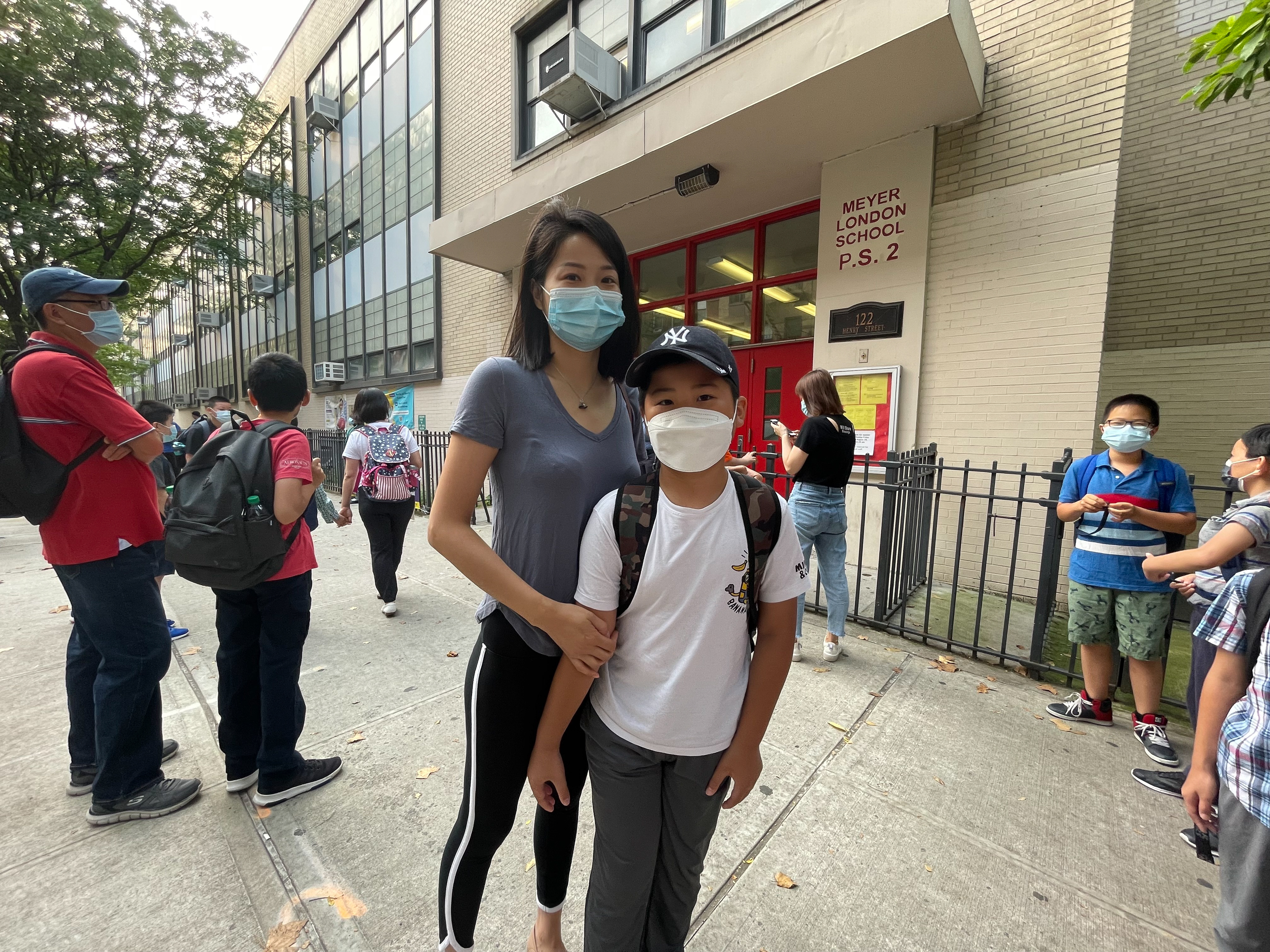 A woman and her son stand in front of a school building among other parents and children for a summer program, all wearing protective masks.