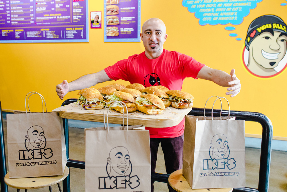 Ike's Love and Sandwiches founder Ike Shehadeh poses with a collection of his generous sized sandwiches.