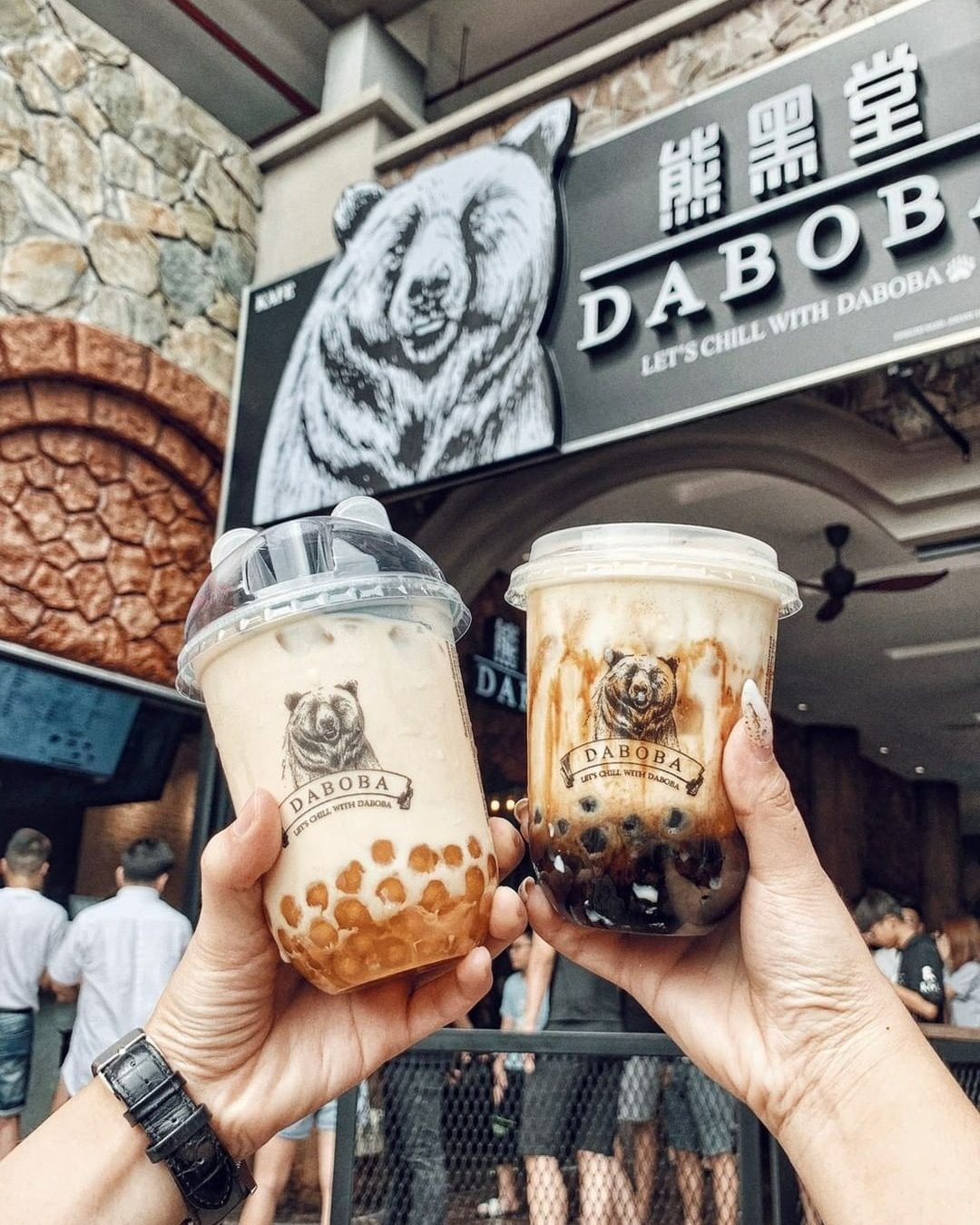 Two hands holding tan drinks in clear cups with tapioca pearls (boba) at the bottom