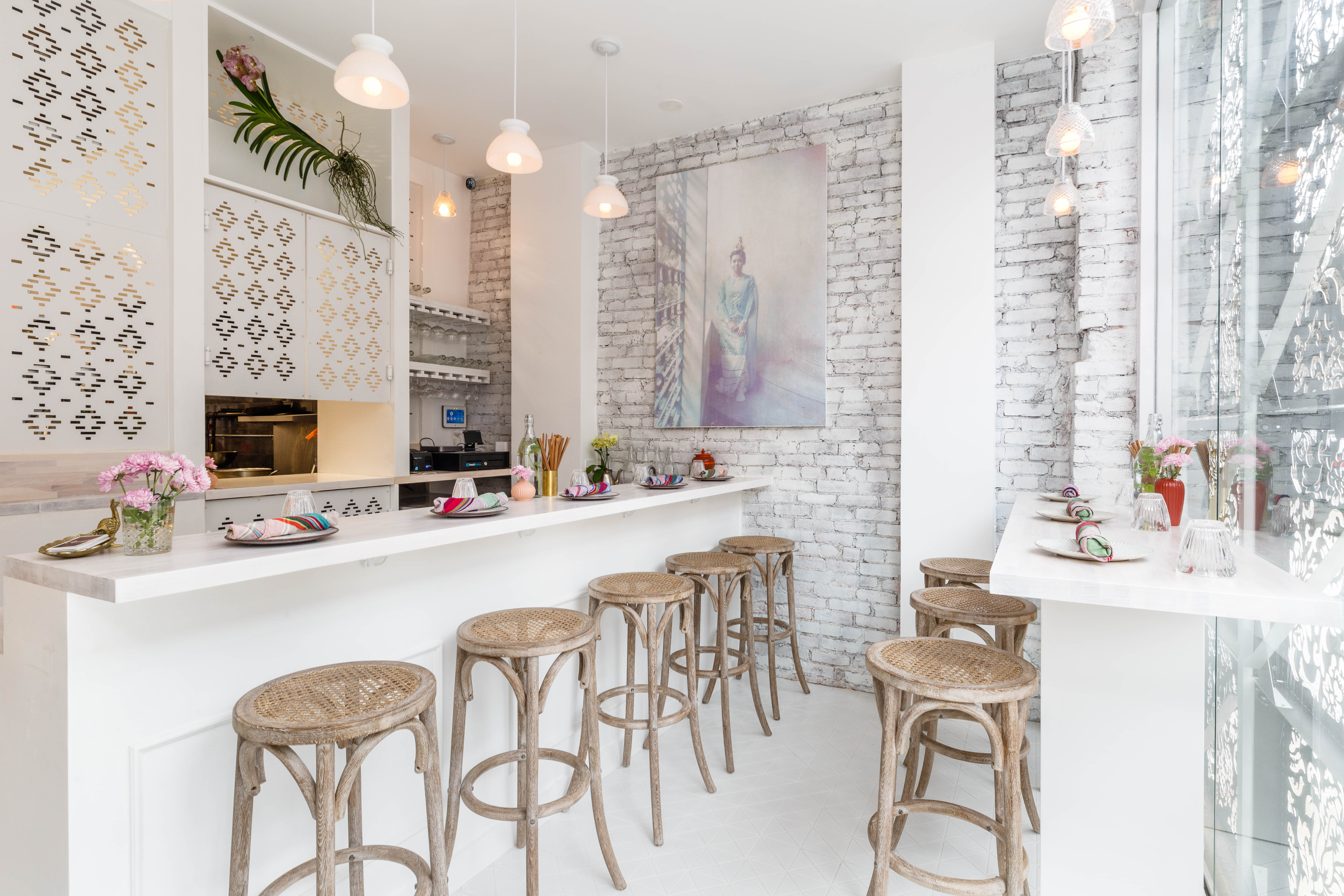 The interior of Burmese restaurant Rangoon which has white counters, wooden stools lined up against it, and exposed brick white walls in the back