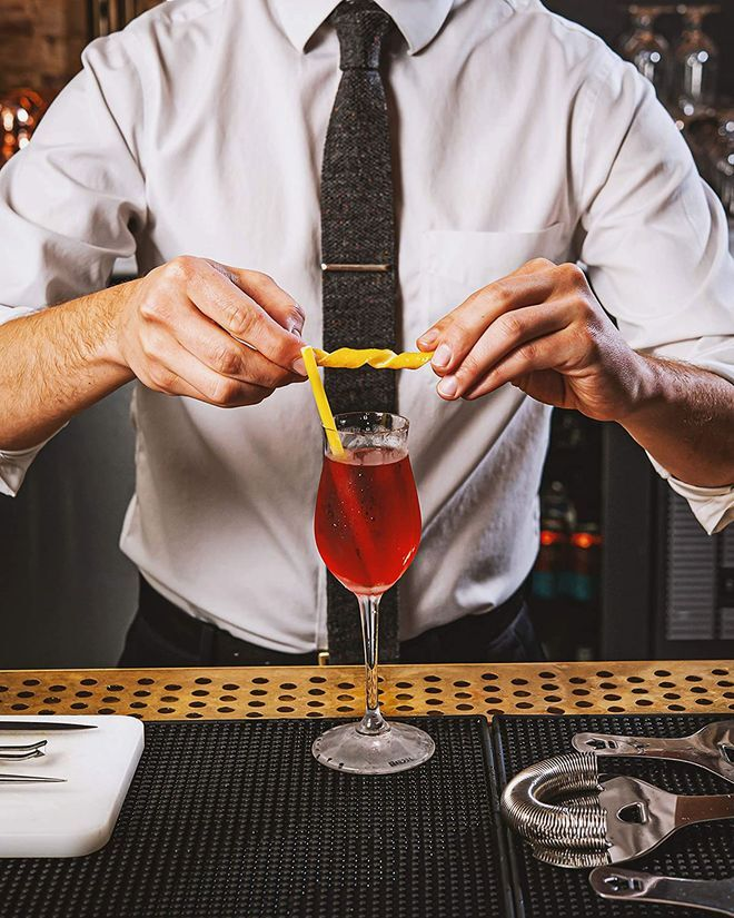 A bartender holds a piece of spiral pasta above a drink with a pasta straw