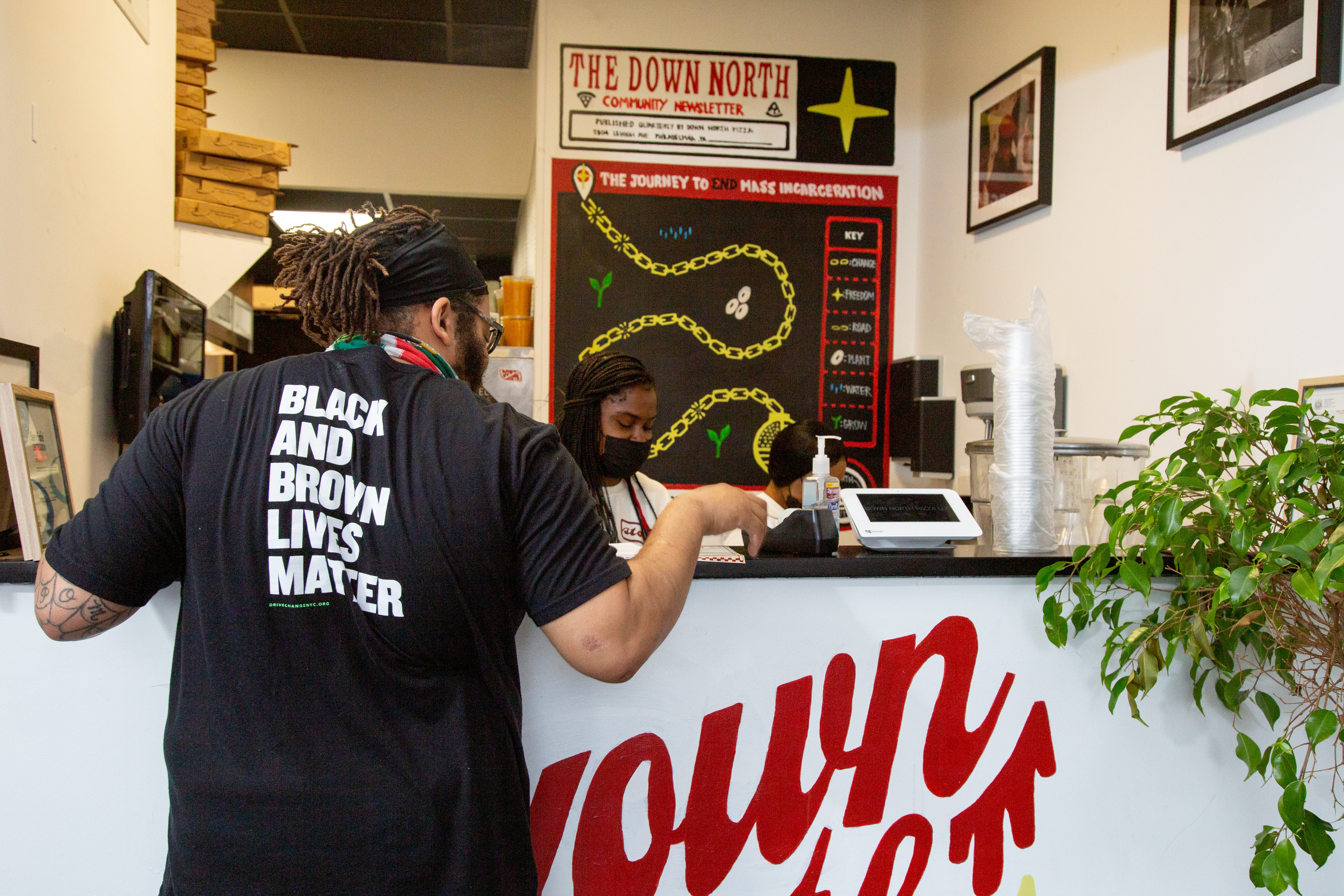 kurt evans stands at a counter at a pizza place with a shirt that says black and brown lives matter