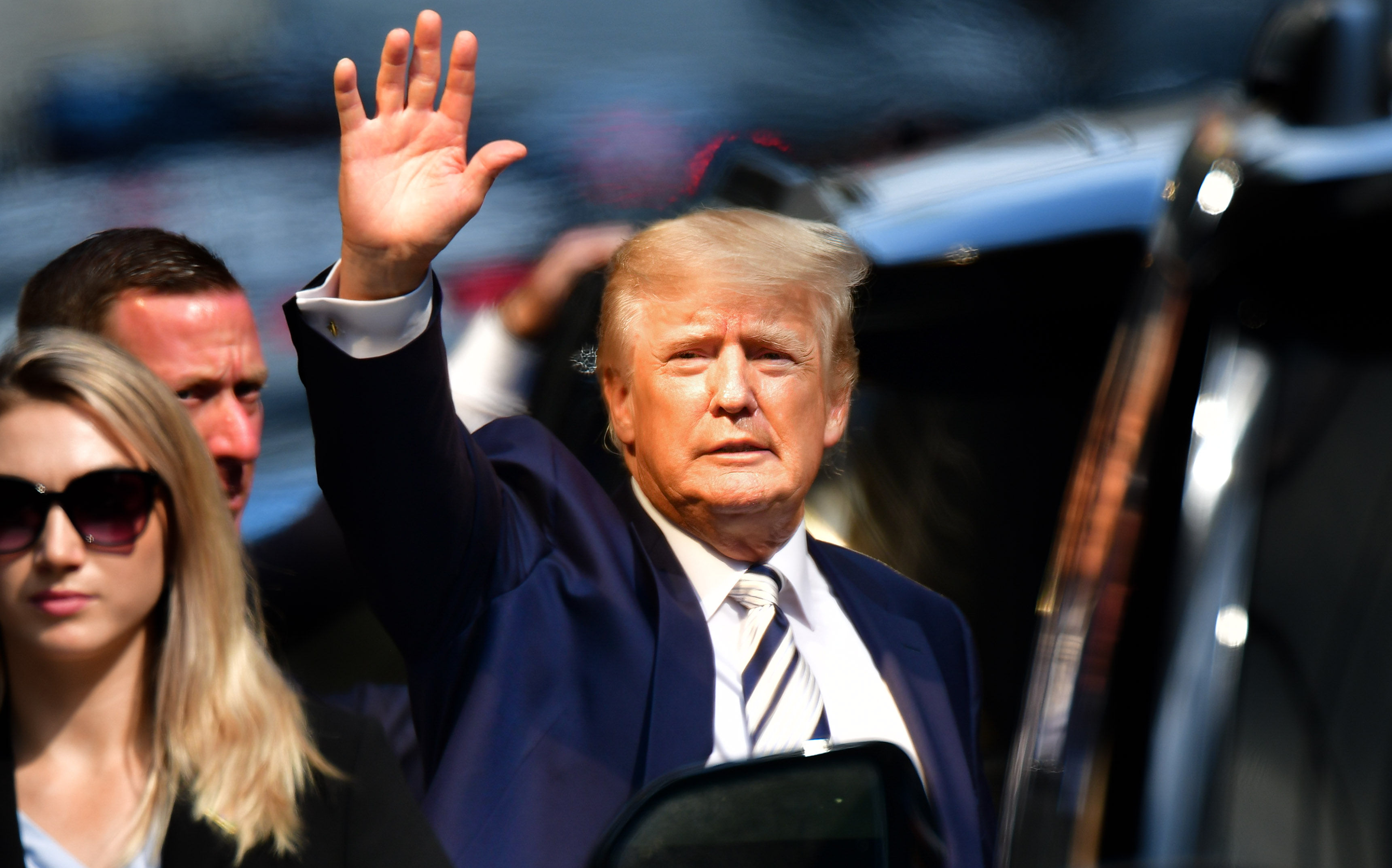 Donald Trump waves as he gets into a car.