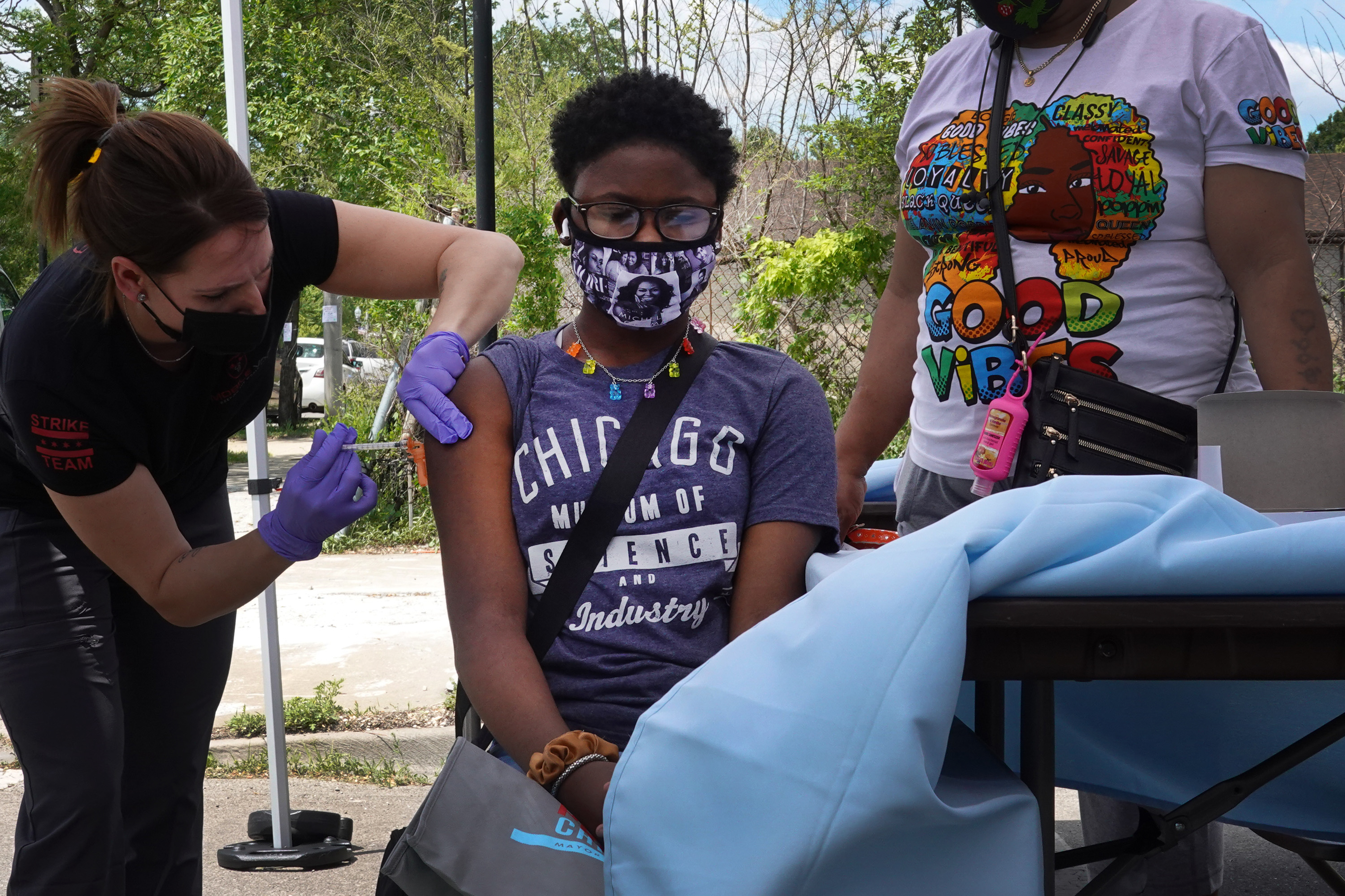 A girl wearing a Chicago shirt stands between two women, one of whom is giving the girl a dose of the COVID vaccine.