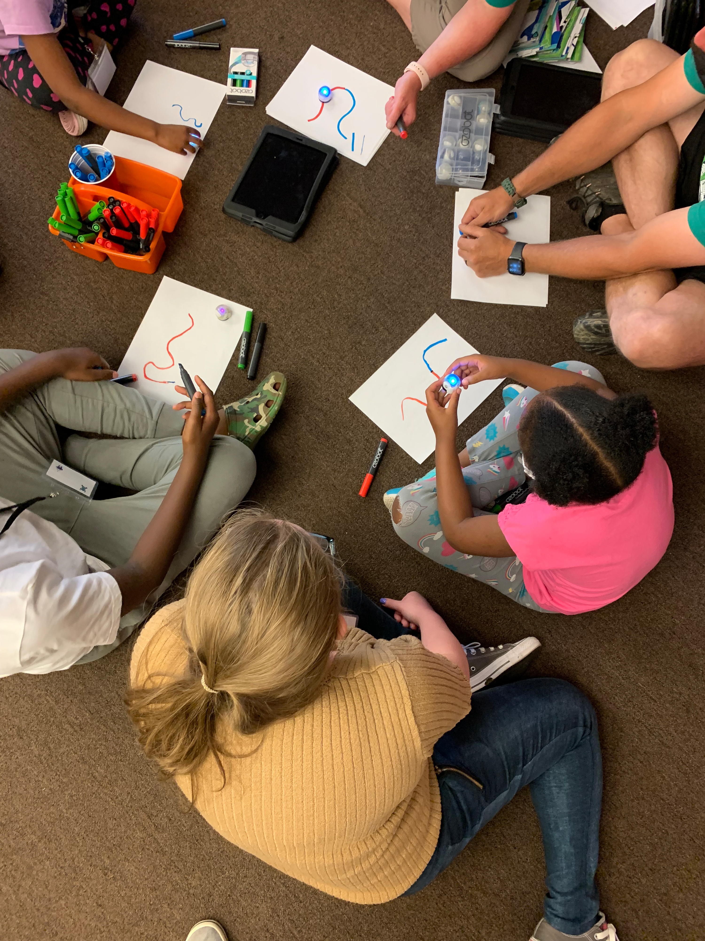 Overhead shot looking down at a tutor and three students sitting on the floor drawing.