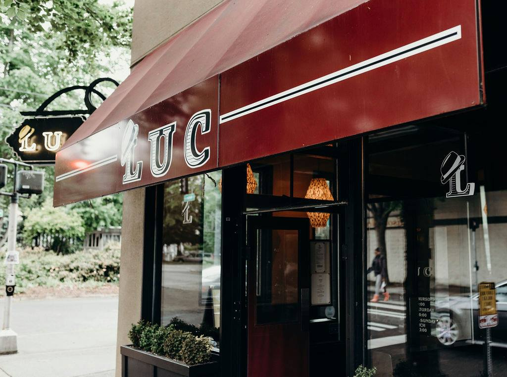 The maroon awning at Luc Bistro in Madison Valley, with the restaurant's name in all caps and white bordering