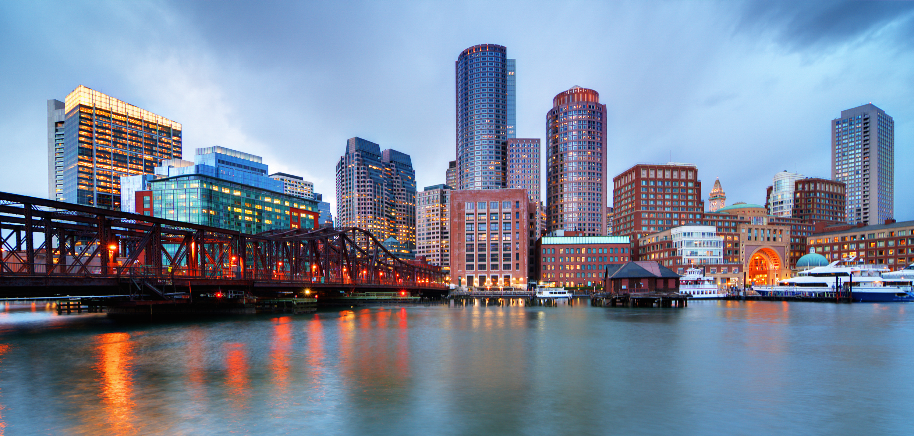 A view of the Boston skyline, featuring Financial District skyscrapers, water, and a cloudy gray sky