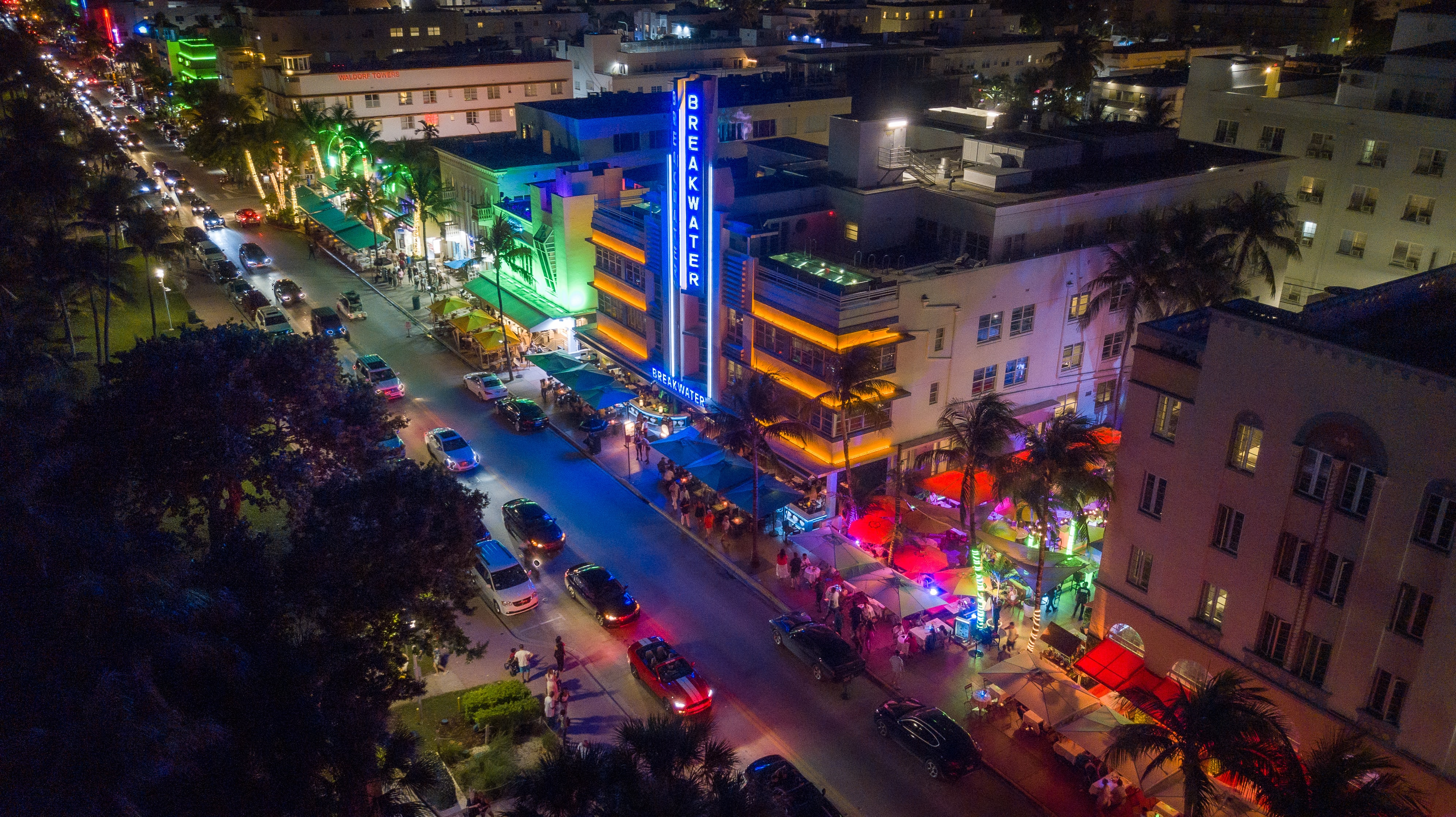 Aerial photo of Ocean Drive at night with bright colors and cars on the street