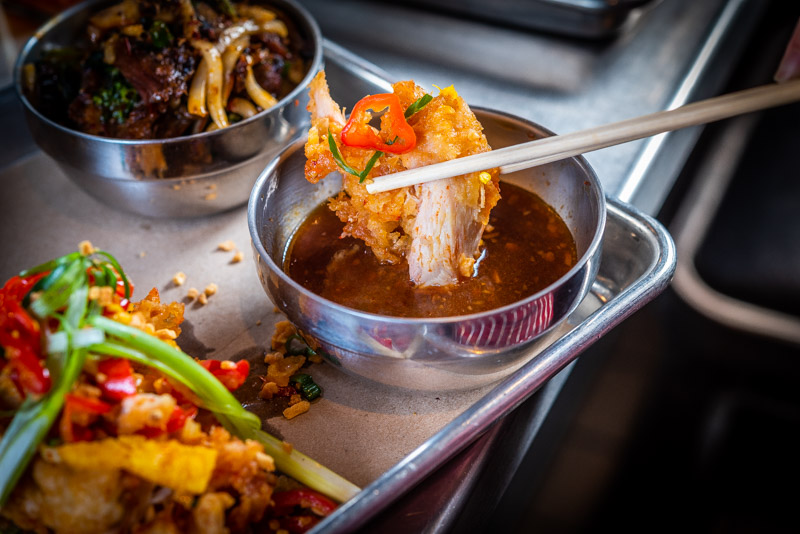 A crispy fried piece of chicken being dipped into a spicy sauce using metal chopsticks, with another cluster of chicken and vegetables on the side.