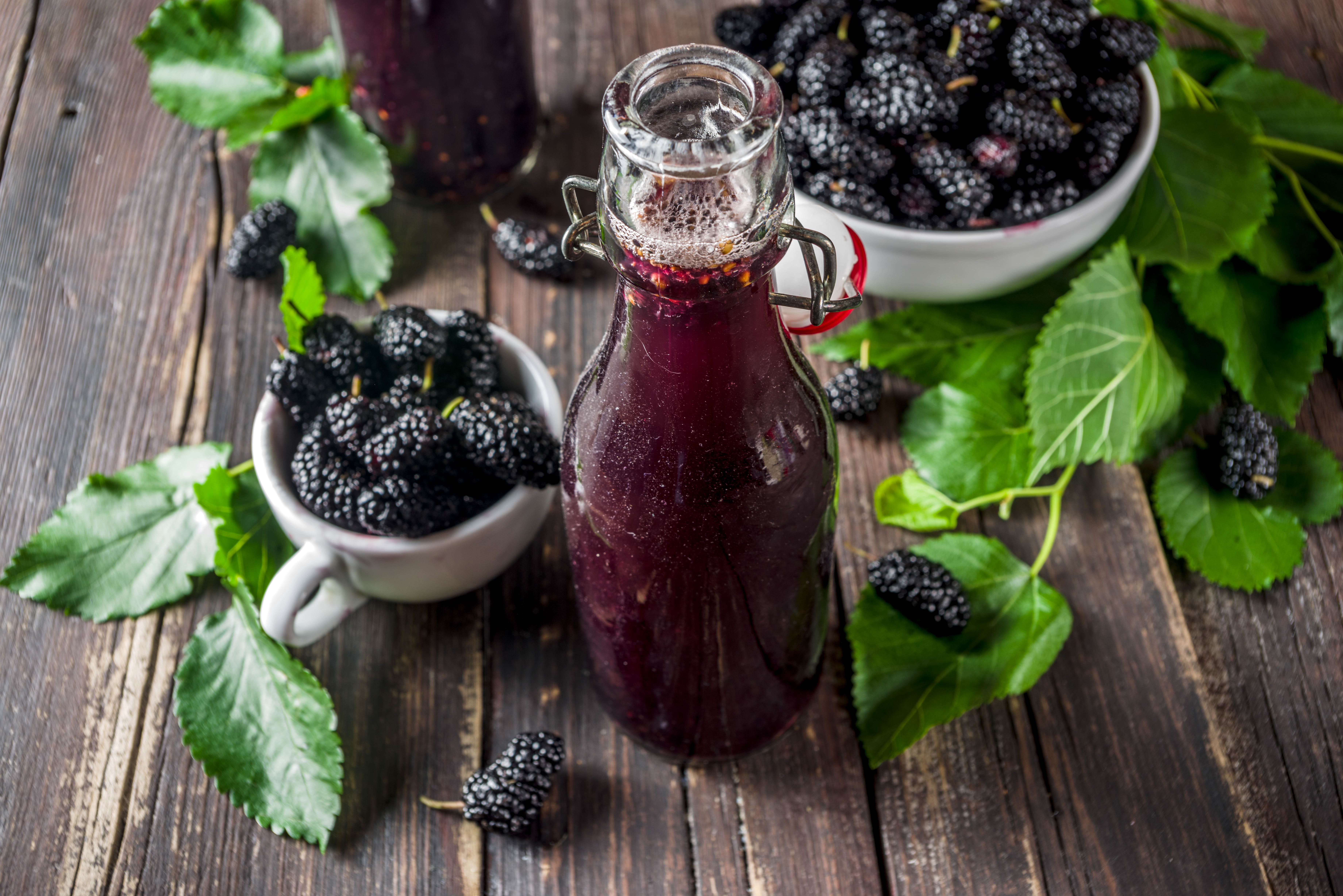 A glass bottle holding a purple mulberry shrub sits on a slatted wooden table with a white plate and teacup full of mulberries and an array of green leaves.