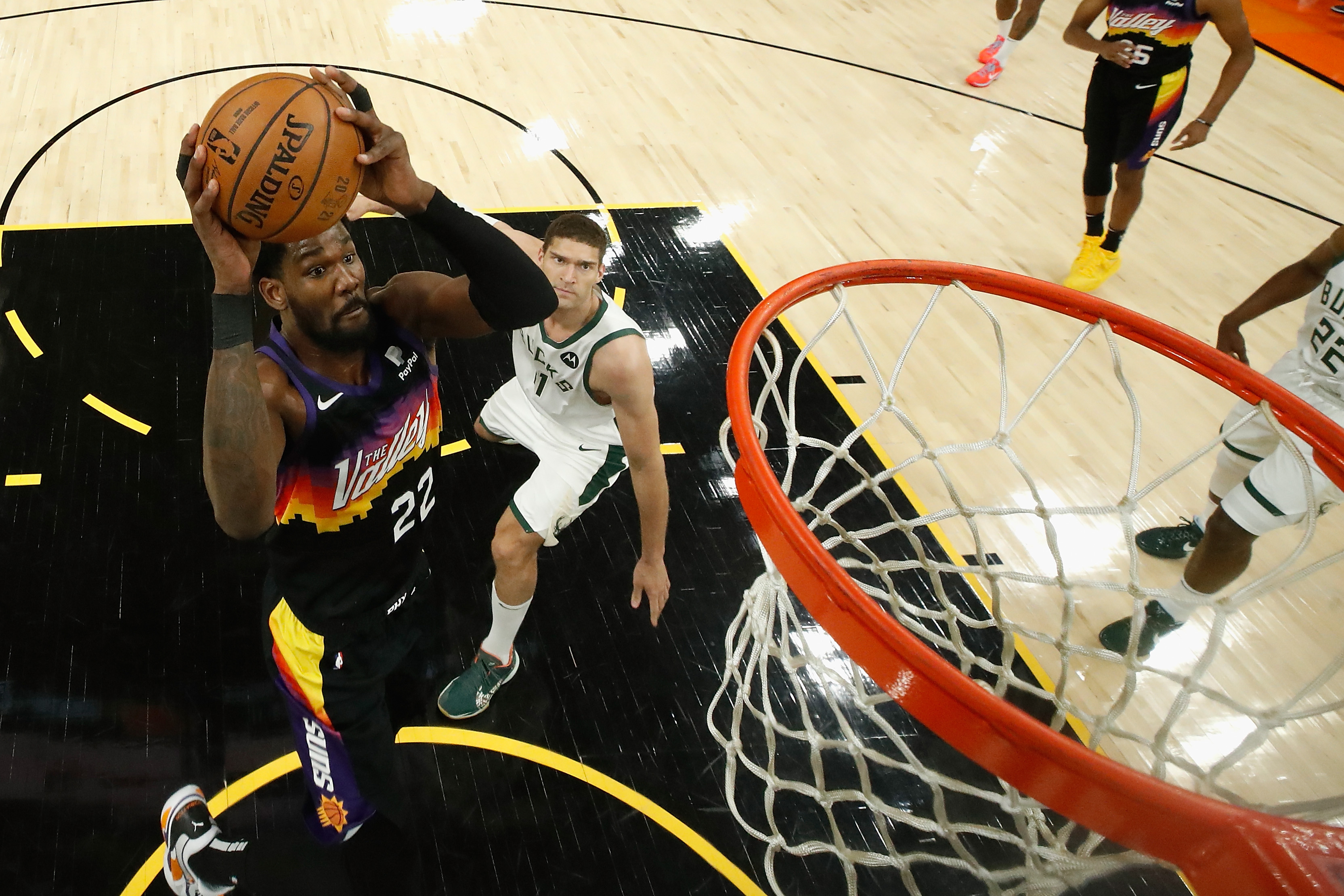 Deandre Ayton of the Phoenix Suns attempts a shot ahead of Brook Lopez of the Milwaukee Bucks during the first half of game one of the NBA Finals at Phoenix Suns Arena on July 06, 2021 in Phoenix, Arizona. The Suns defeated the Bucks 118-105.