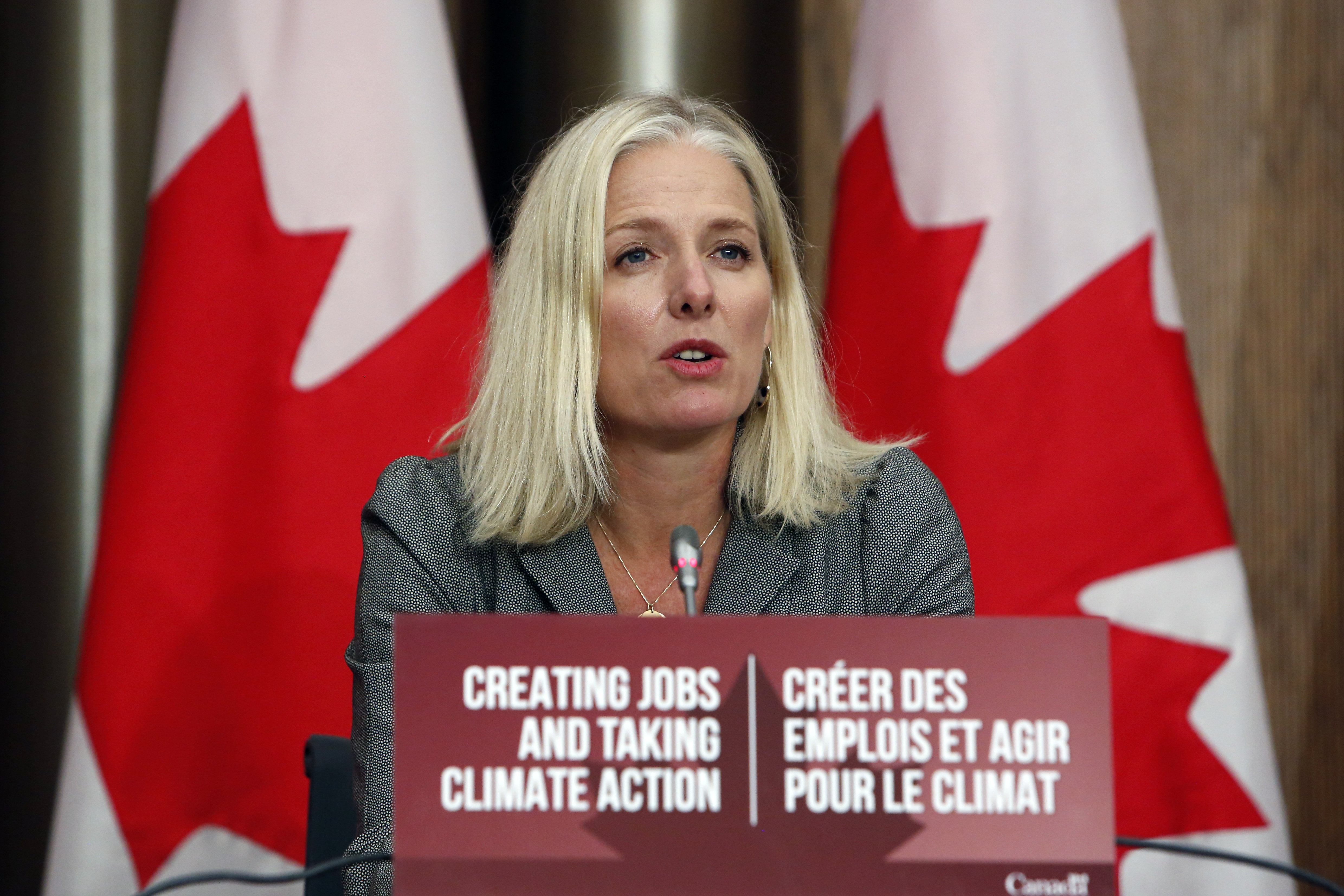 """Catherine McKenna, Canada's infrastructure and communities minister, speaks during a news conference in Ottawa, Ontario, Canada, on Thursday, October 1, 2020. She is speaking in front of a sign that reads """"Creating jobs and taking climate action"""" in English and in French. Two red-and-white Canadian flags stand behind her."""