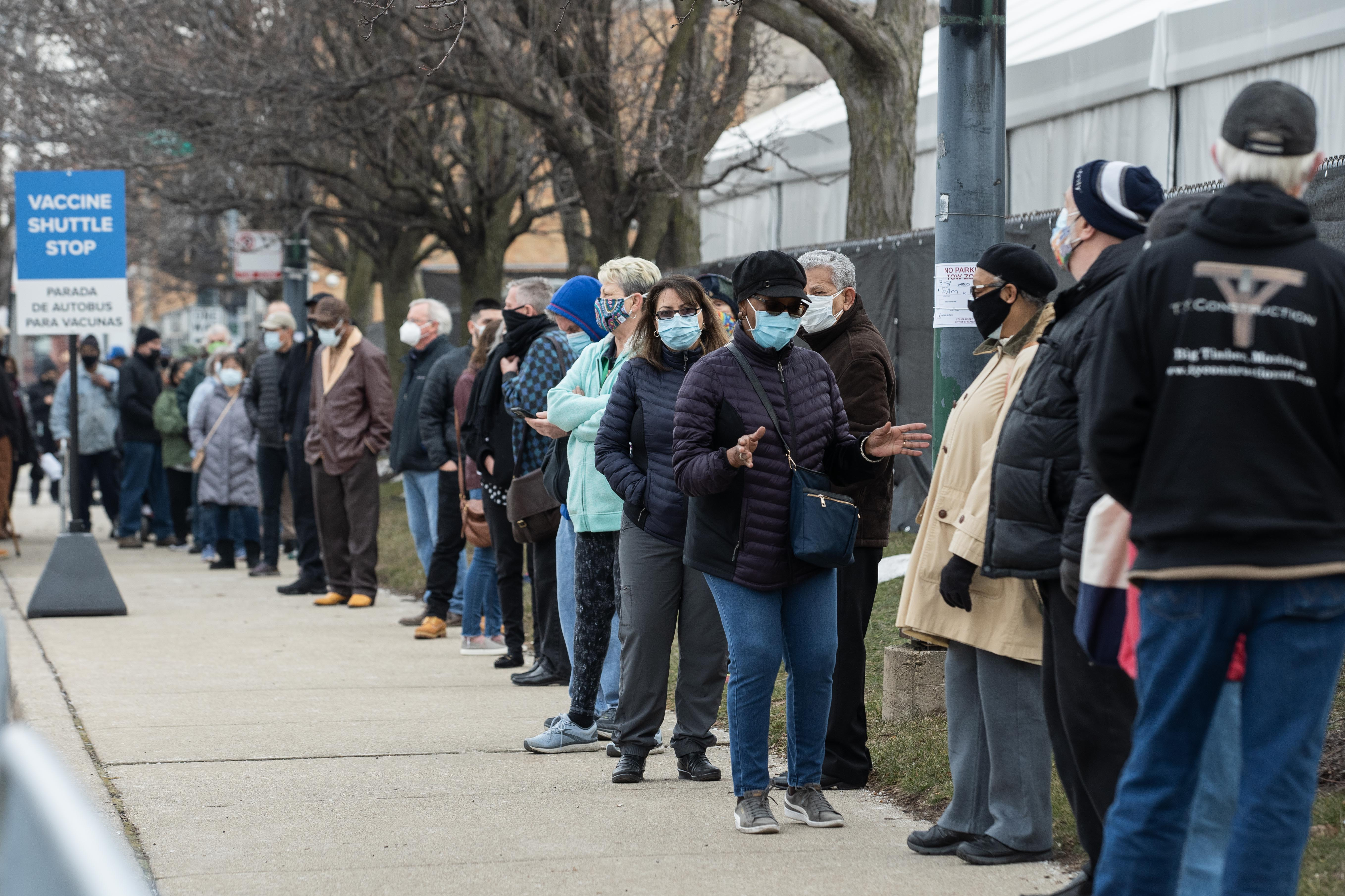People line up outside the COVID-19 mass vaccination site in a parking lot of the United Center in March.