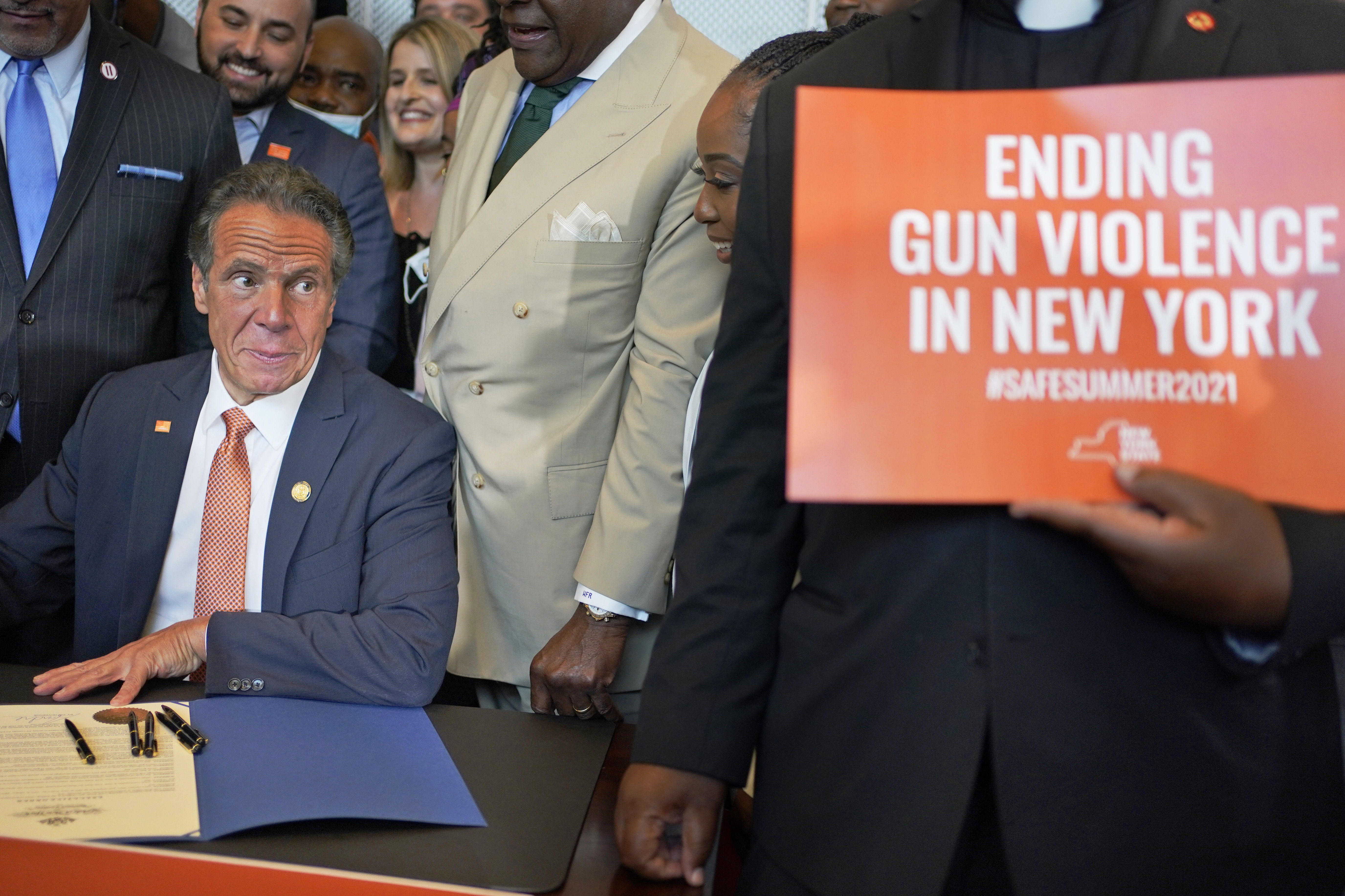 Surrounded by supporters and advocates, New York Gov. Andrew Cuomo signs legislation on gun control in New York on Tuesday. Cuomo signed two pieces of legislation to combat gun violence in New York state.