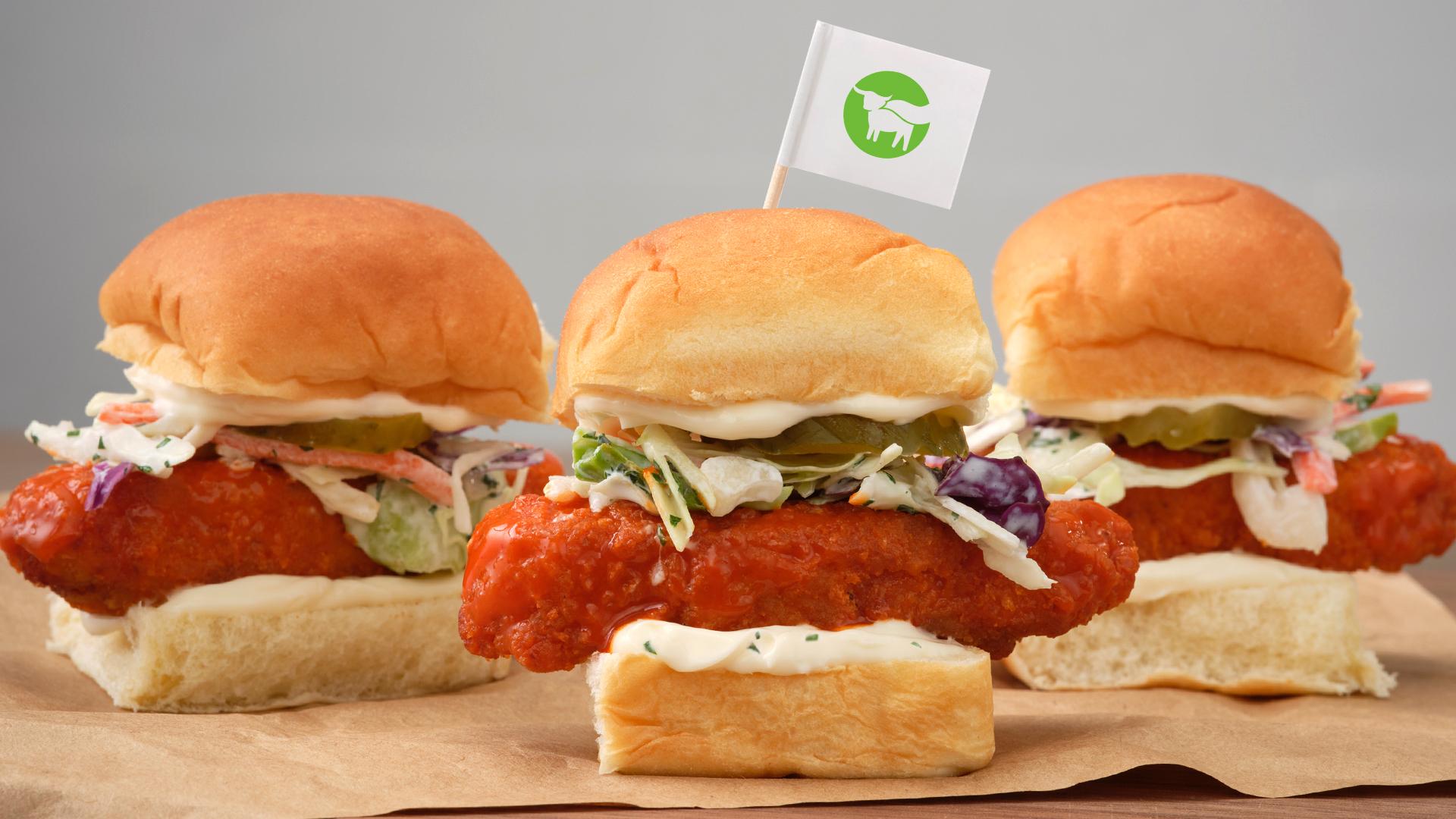 Three plant-based chicken sandwiches on small hamburger-style buns.