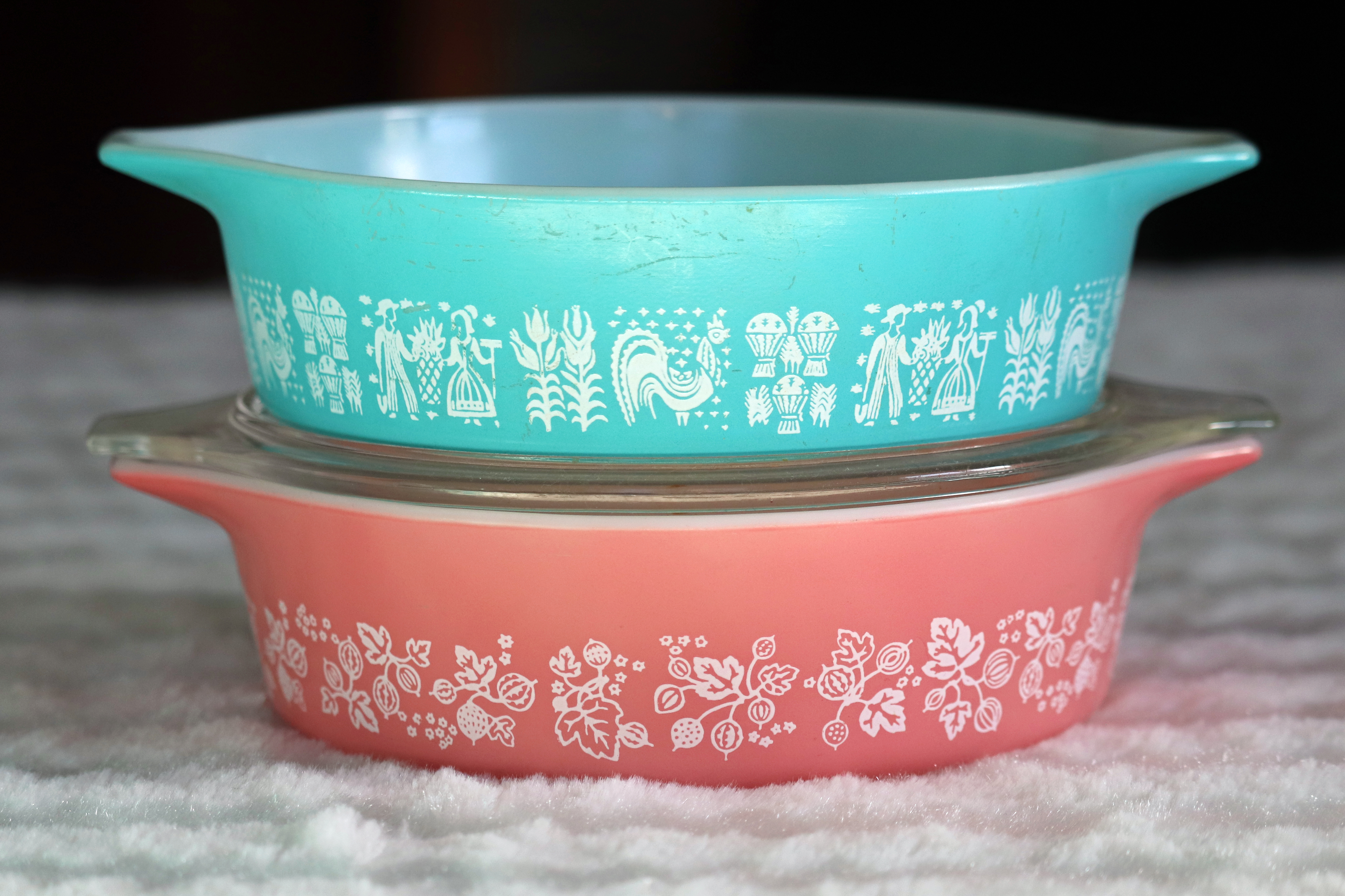 """An aqua blue Pyrex casserole dish with a farm scene  """"Amish butterprint"""" design stacked on top of a pink Pyrex casserole dish with a gooseberry print displayed on a white towel."""