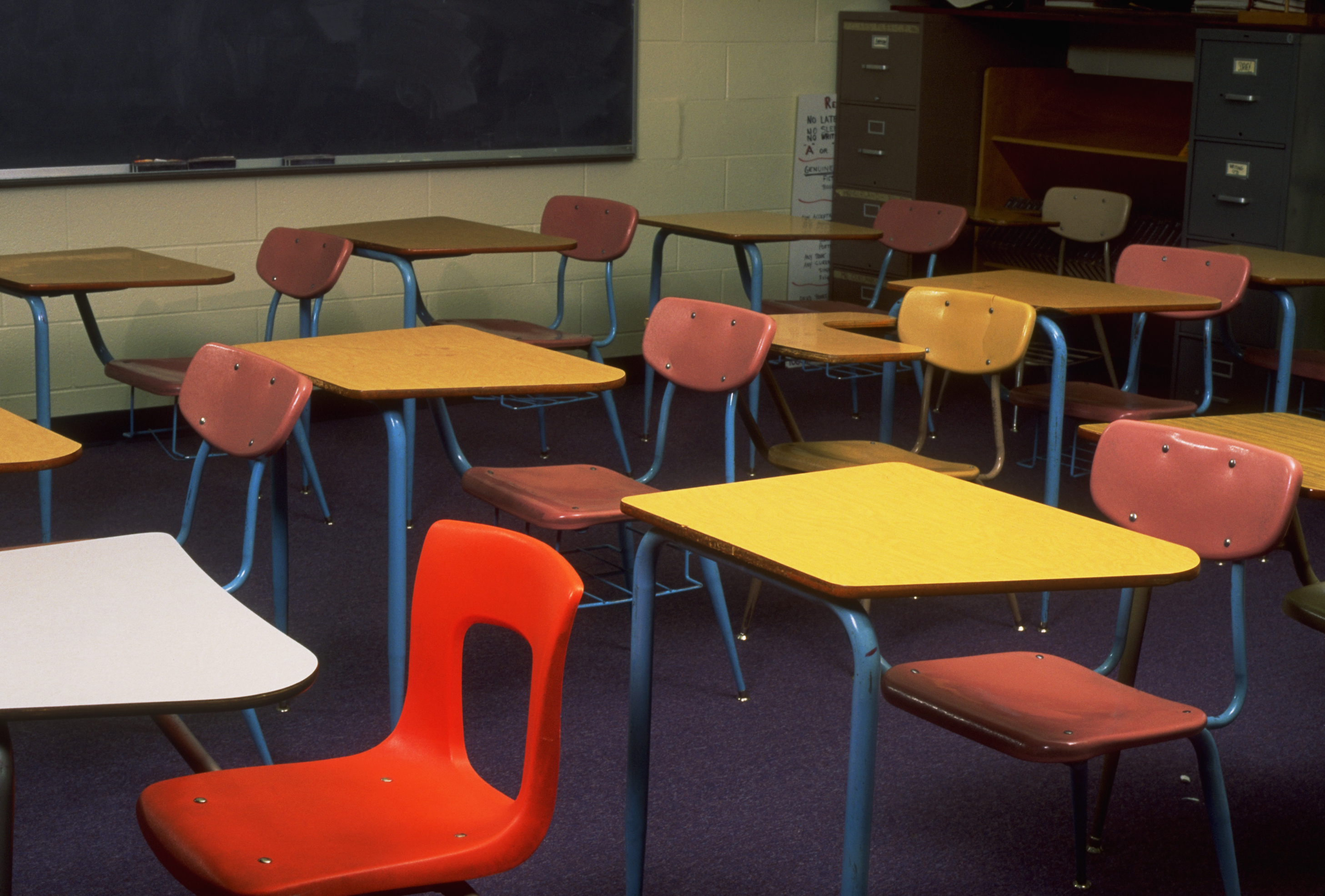 Colorful empty school desks and chairs in a classroom.