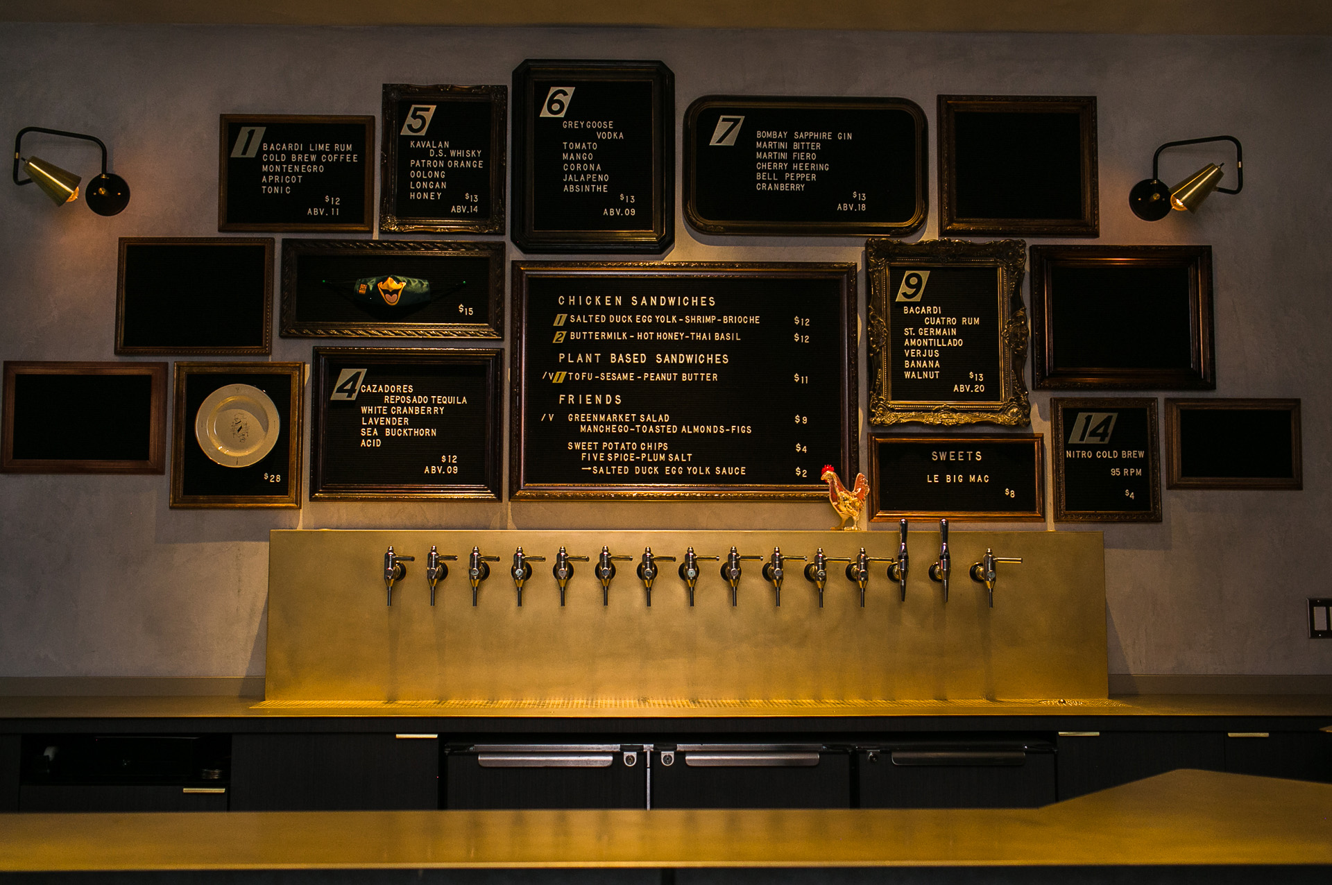 Several sandwich board signs hang on a wall together, advertising food and drink specials in a dimly lit bar