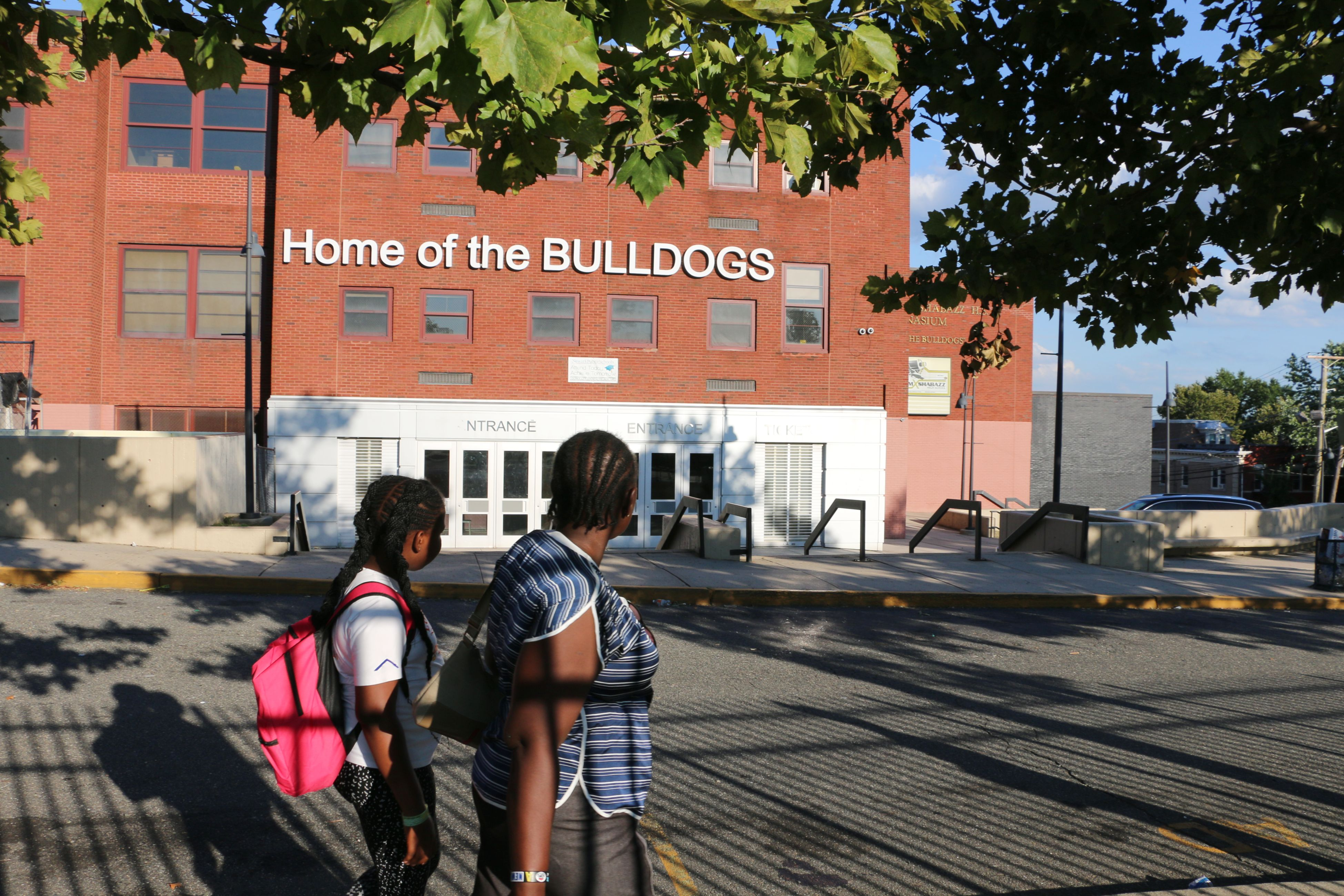 In the foreground, a student wearing a pink backpack stands behind an adult in a blue-striped shirt as they face Malcolm X Shabazz High School in the background.