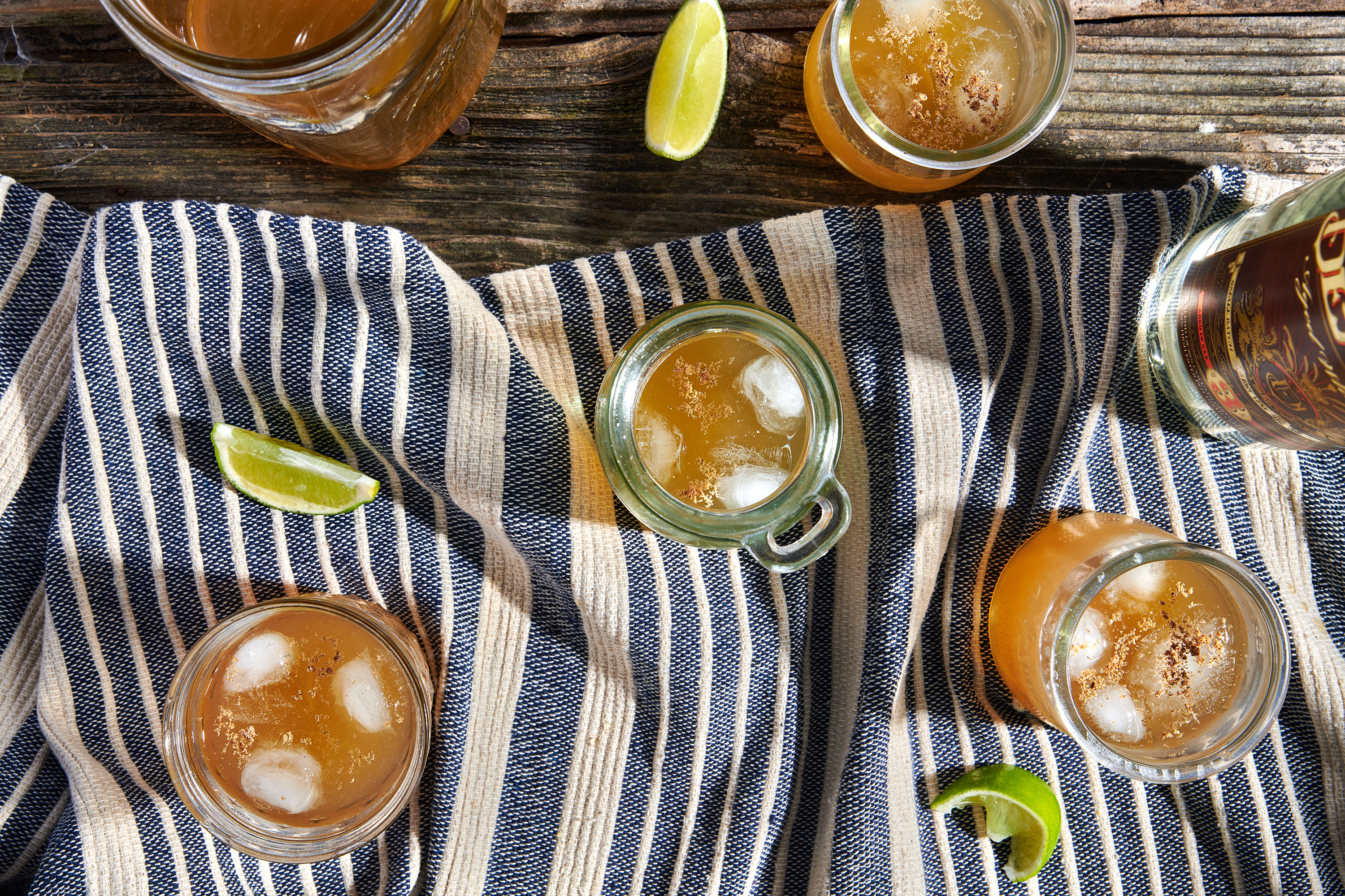 Mason jars filled with ice and orange liquid as seen from above on a picnic table, with blue and white table runner and lime wedges alongside.