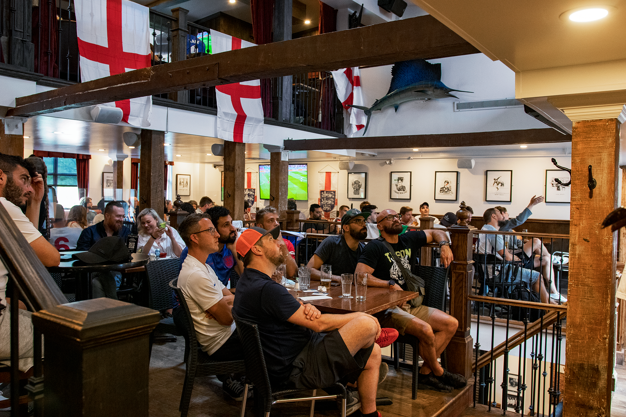 people in pub watching screen with England fans in the background