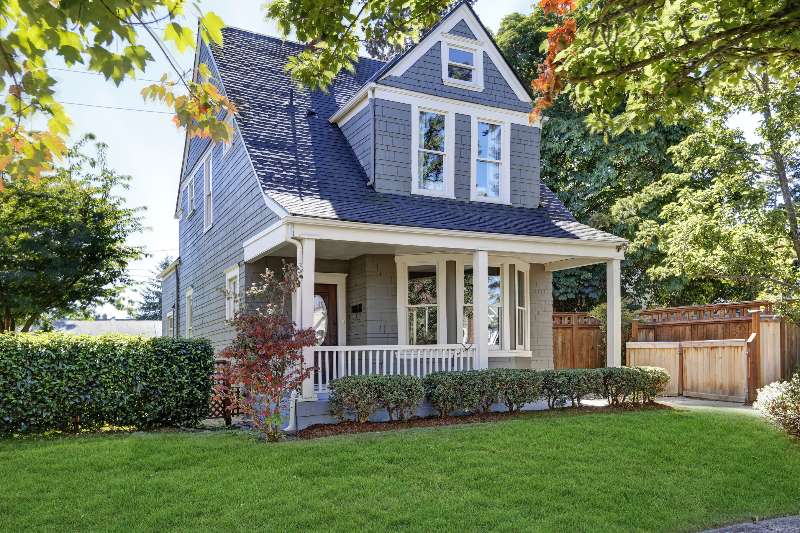 A grey-blue home with a large front porch, large green front yard, and several green shrubs.