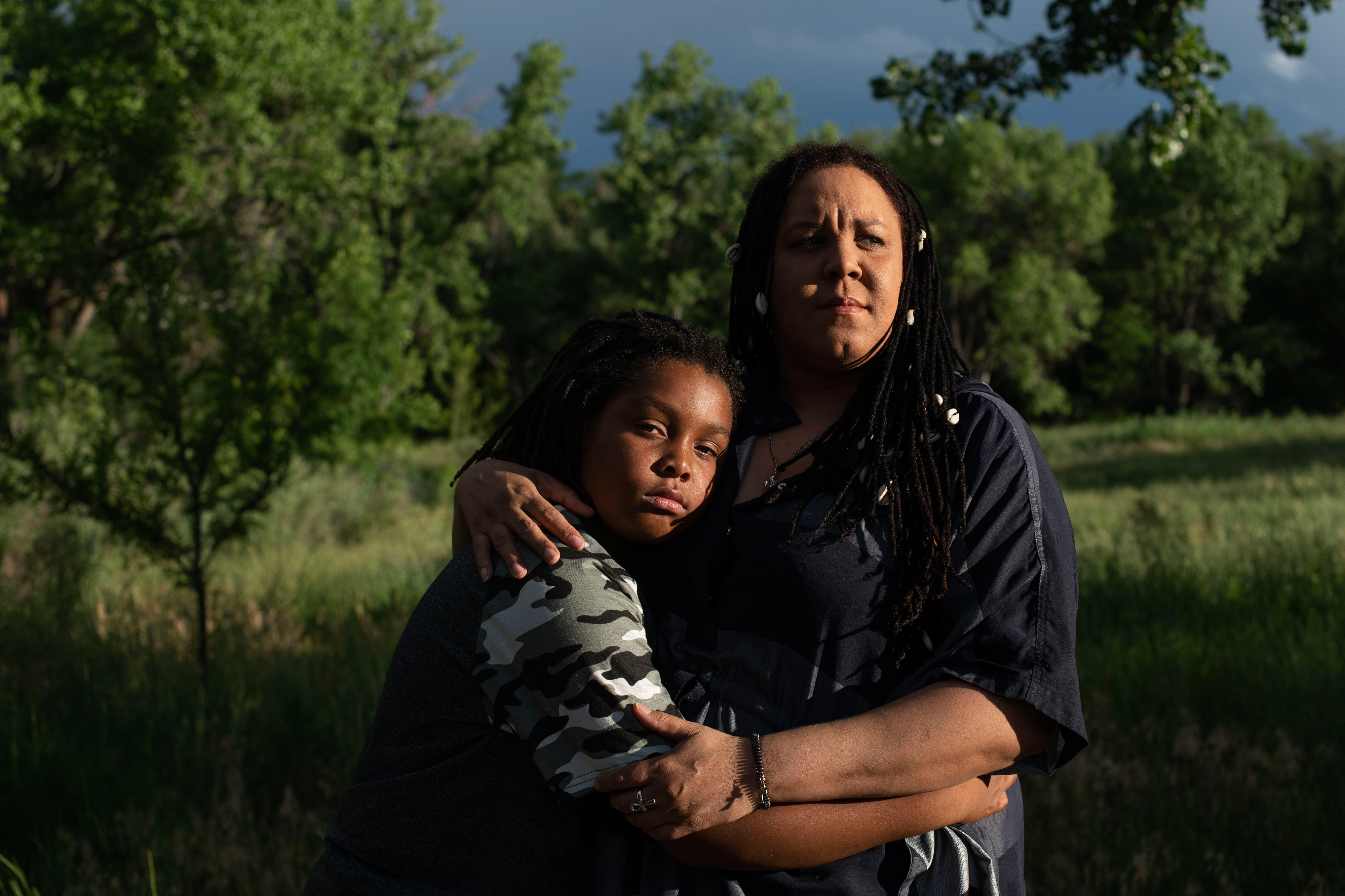A mother and her 11-year-old son embrace in a park. They are both looking at the camera with serious expressions on their faces.