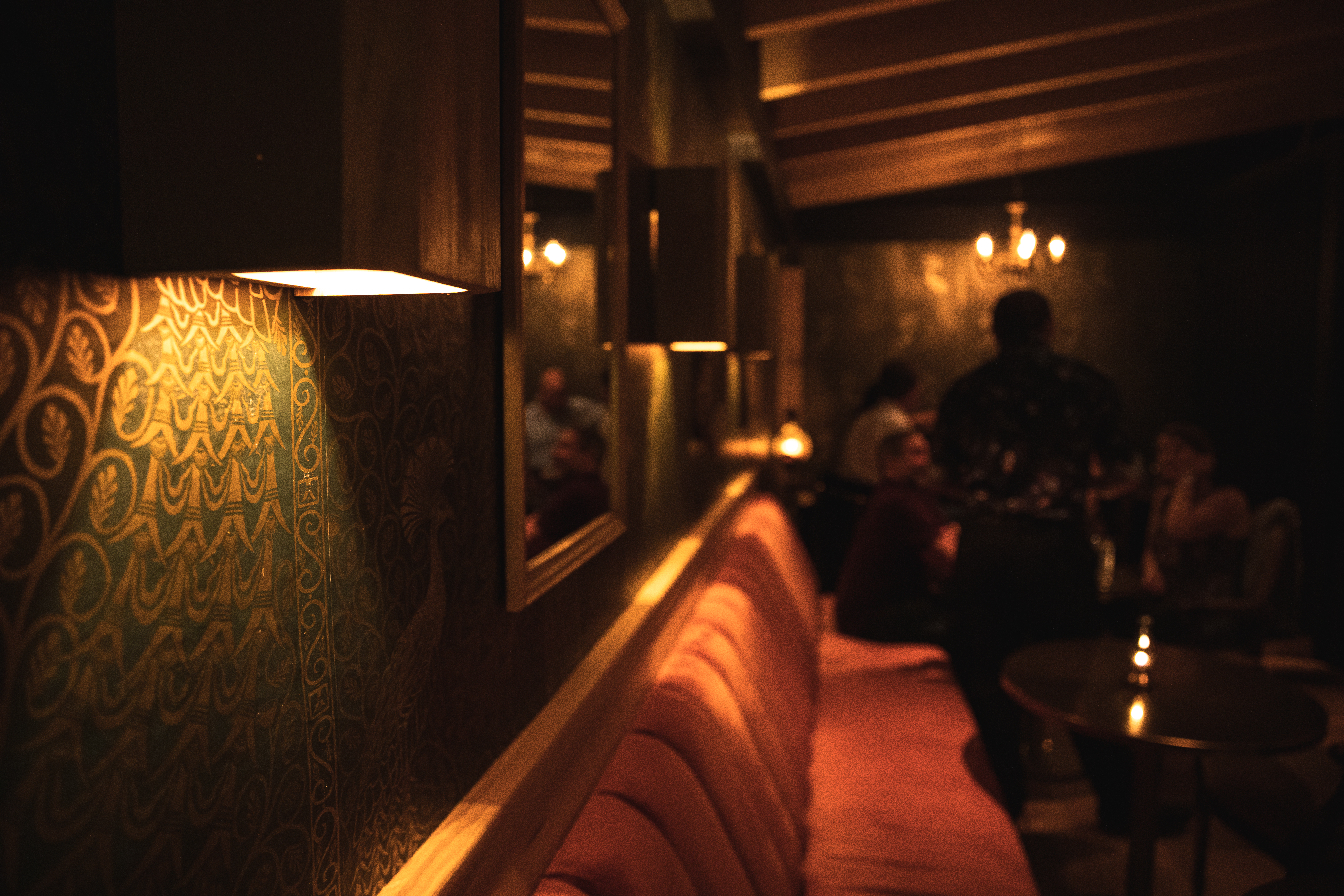 The interior of Dallas cocktail bar Apothecary, with peacock-printed wallpaper and velvet banquettes
