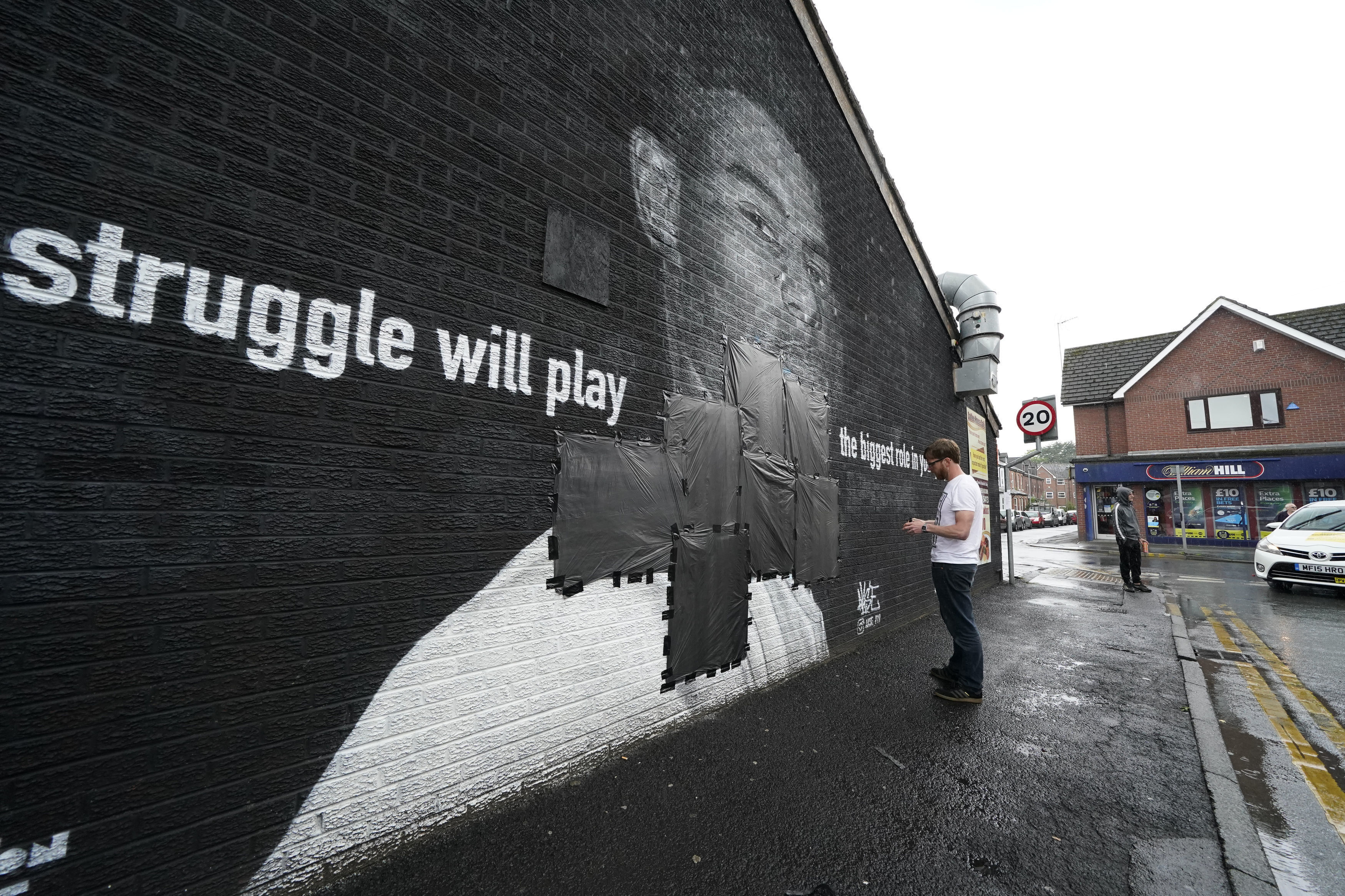 Ed Wellard tapes trash can liners across offensive wording on the mural of Manchester United striker and England player Marcus Rashford.