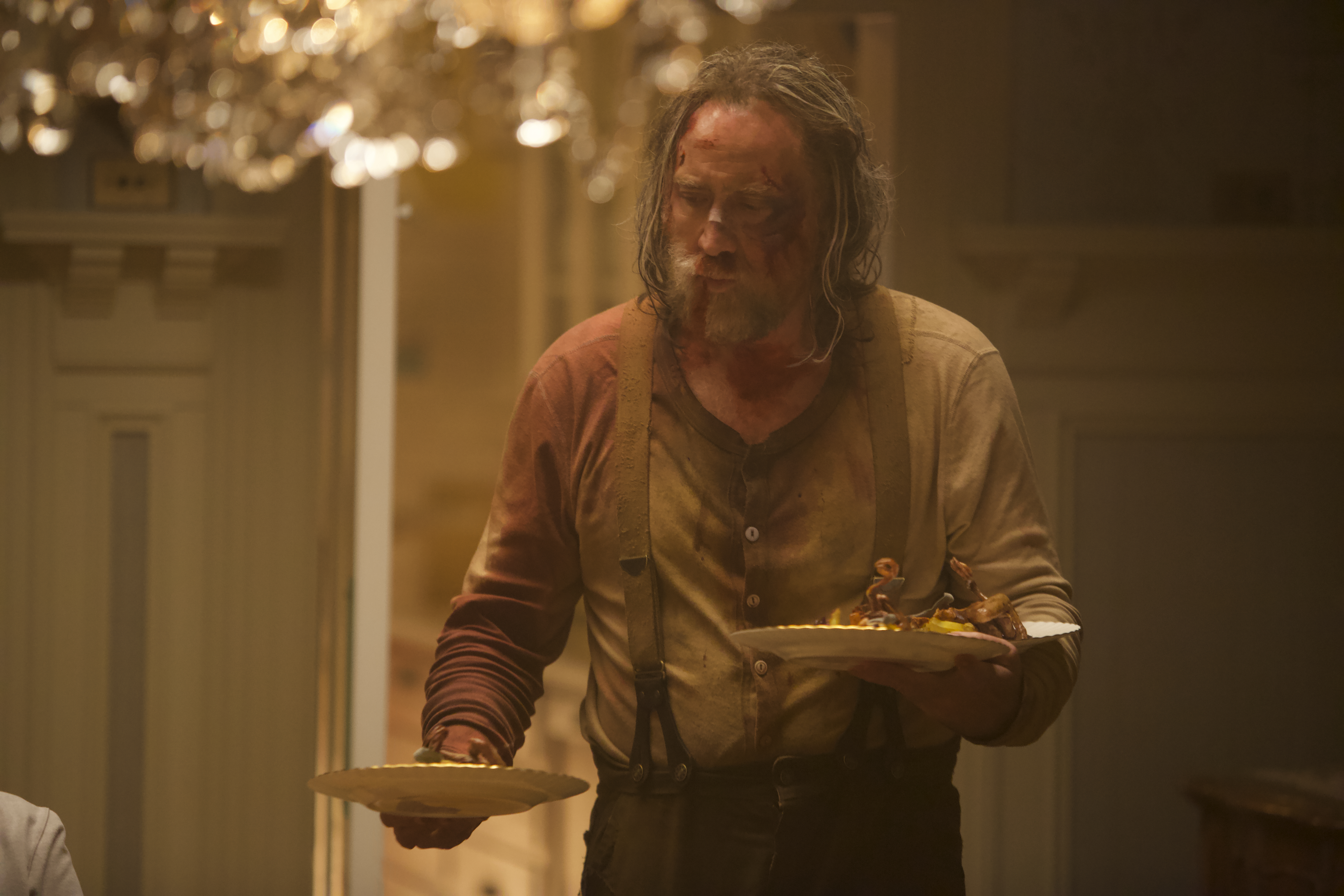 A still from the movie 'Pig,' featuring Nicolas Cage looking bruised and bloody, carring three plates of food in his arms.